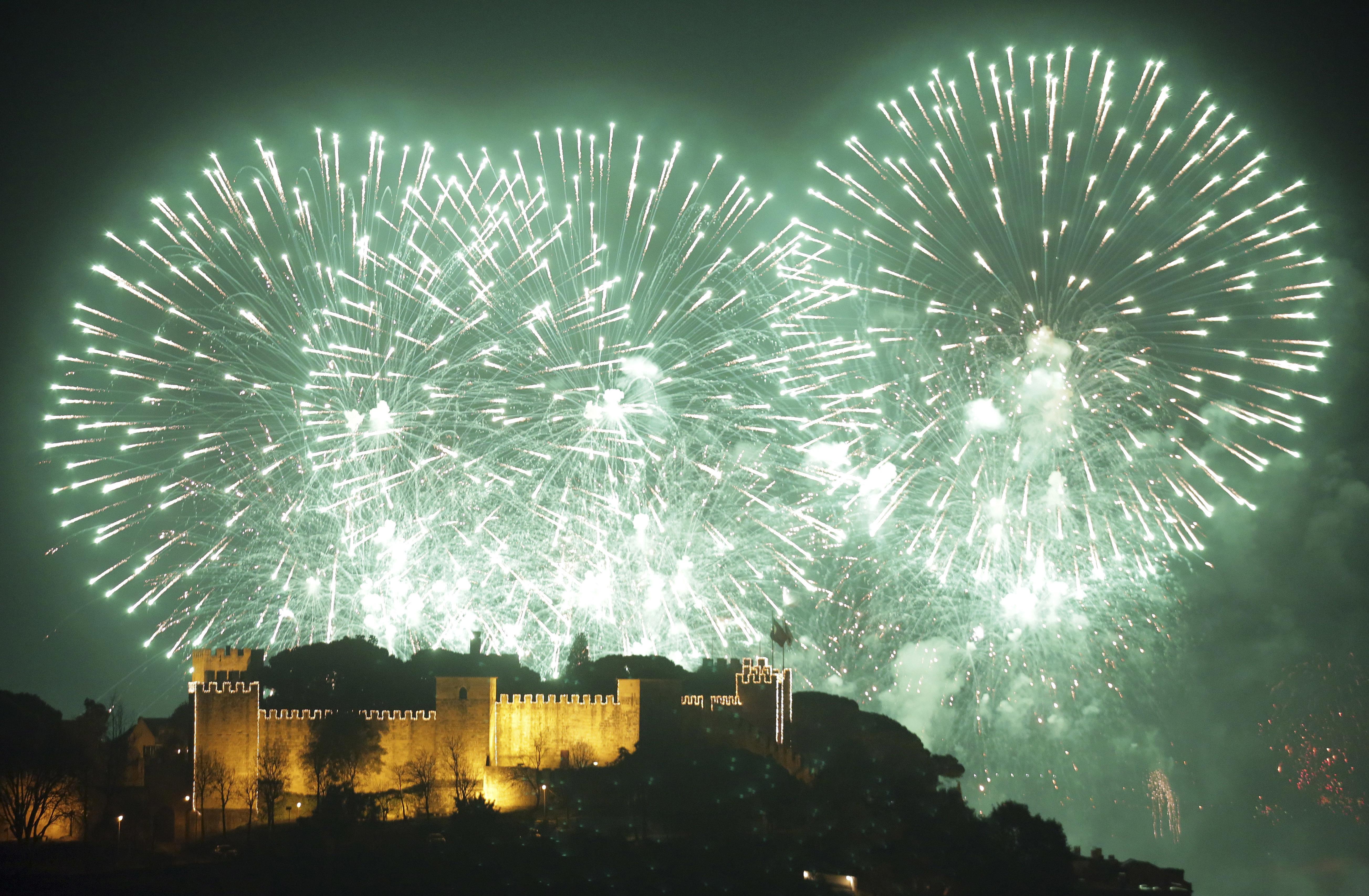 Fuegos artificiales iluminan el cielo por el Año Nuevo detrás del castillo de San Jorge en Lisboa(AP Foto/Armando Franca)