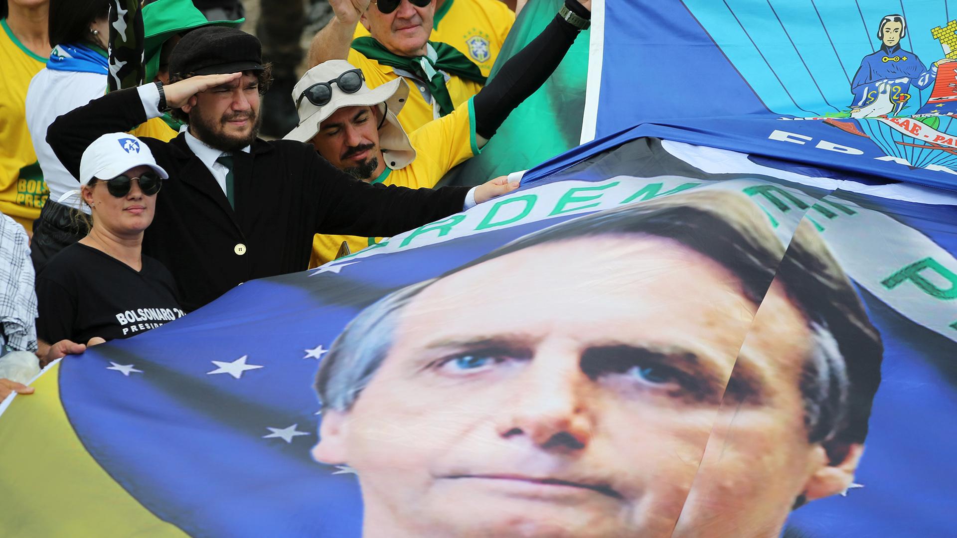 Los seguidores sostienen una bandera con el rostro de Bolsonaro (REUTERS/Sergio Moraes)