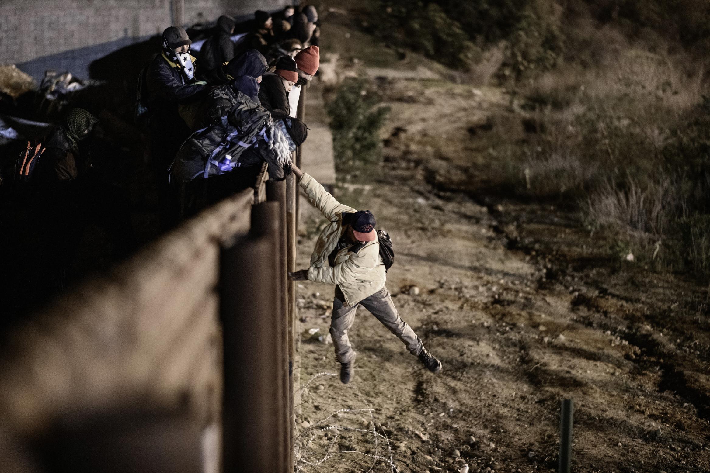 Los agentes de protección de la frontera de EE. UU. Envían a los migrantes a la parte mexicana de la valla fronteriza después de que subieron la valla para llegar a San Diego, California, desde Tijuana, México, el martes 1 de enero de 2019. (Foto AP / Daniel Ochoa de Olza)