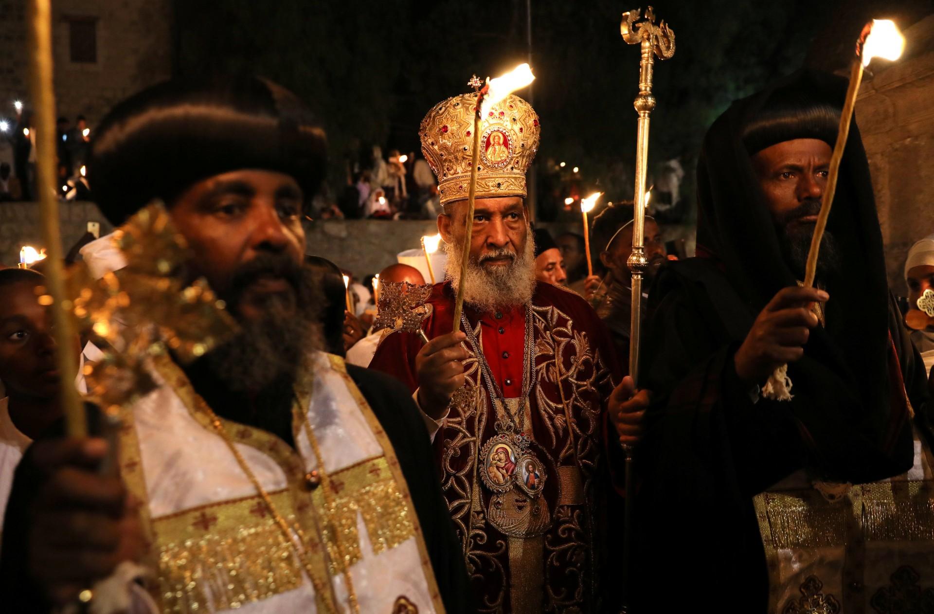El arzobispo Abune Enbakom, de la Iglesia Ortodoxa Etíope en Jerusalén (C), participa en la ceremonia del Fuego Sagrado en la sección etíope de la Iglesia del Santo Sepulcro en la Ciudad Vieja de Jerusalén, el 7 de abril de 2018.