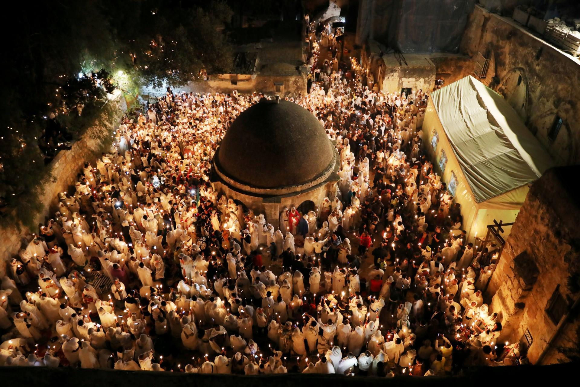 Los adoradores ortodoxos etíopes sostienen con velas durante la ceremonia del Fuego Sagrado en la sección etíope de la Iglesia del Santo Sepulcro en la ciudad vieja de Jerusalén, el 7 de abril de 2018.