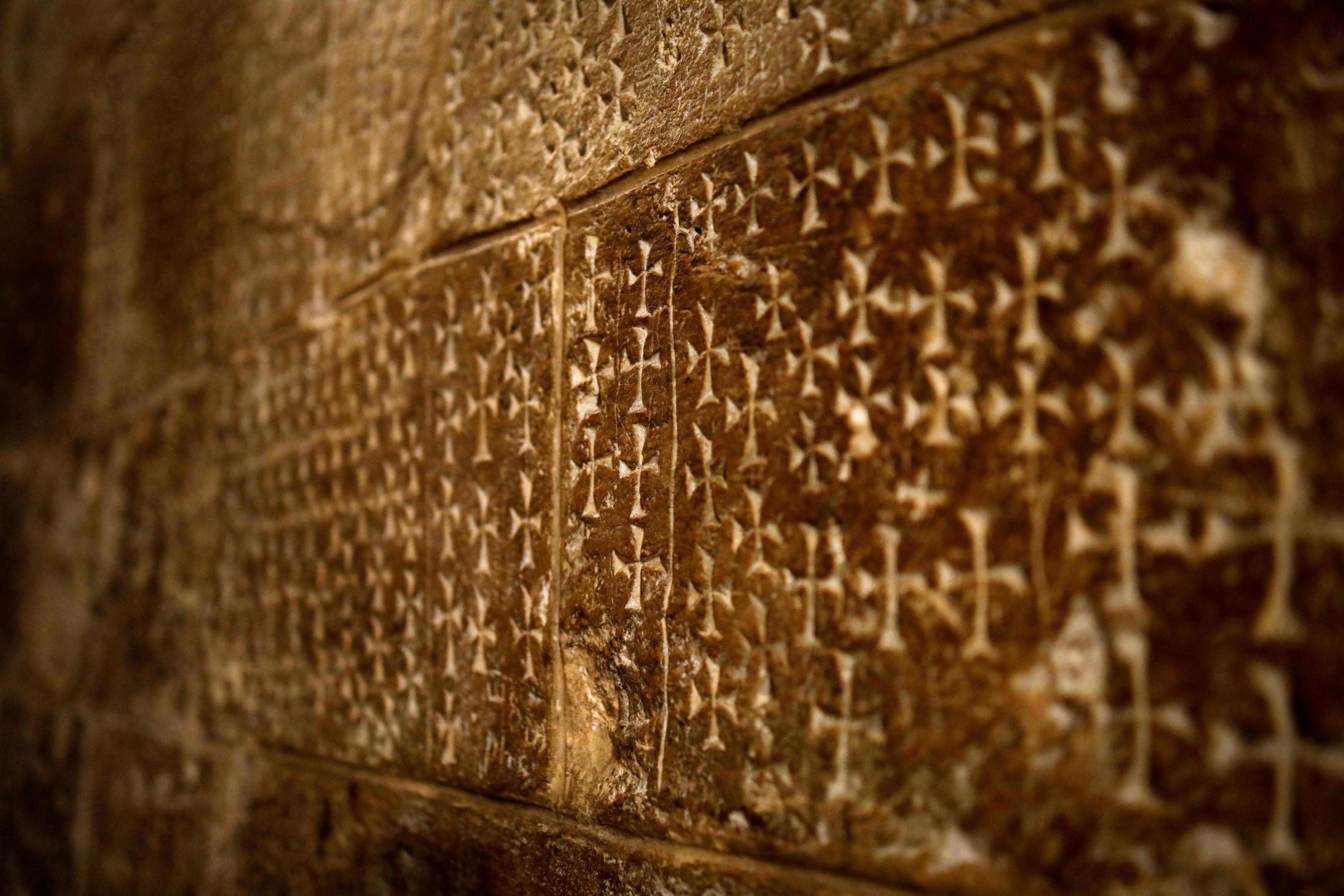 Las cruces talladas en la pared por peregrinos se ven junto a las escaleras que conducen a la Cripta de Santa Elena en la Iglesia del Santo Sepulcro en la Ciudad Vieja de Jerusalén, el 27 de marzo de 2018.