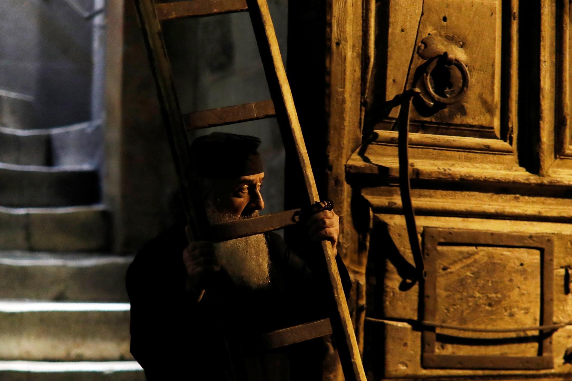 Un sacerdote cristiano ortodoxo sostiene una escalera cerca de la puerta de entrada de la Iglesia del Santo Sepulcro en la Ciudad Vieja de Jerusalén, 17 de noviembre de 2018.