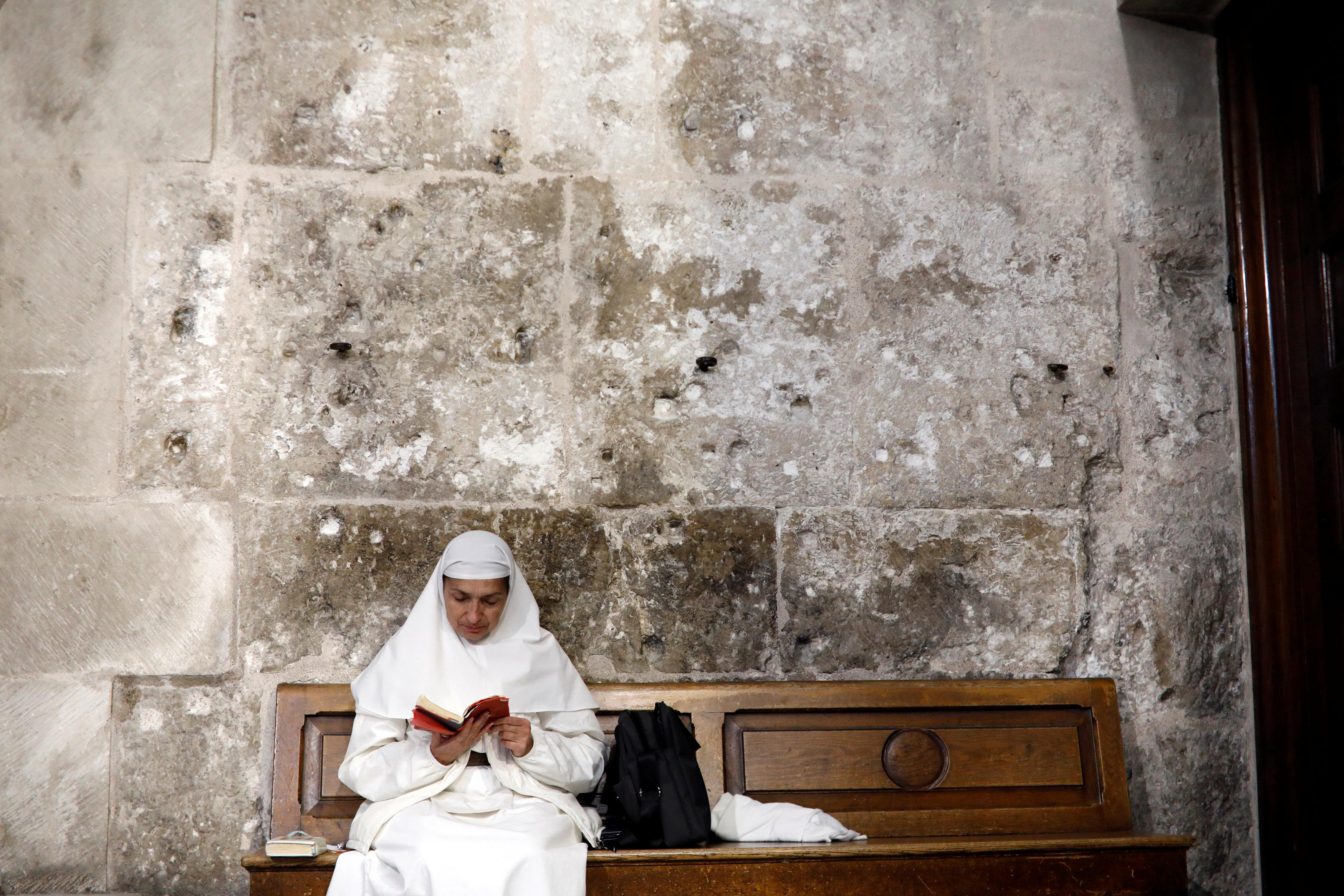 Una monja se sienta en un banco dentro de la Iglesia del Santo Sepulcro en la ciudad vieja de Jerusalén, 17 de noviembre de 2018.