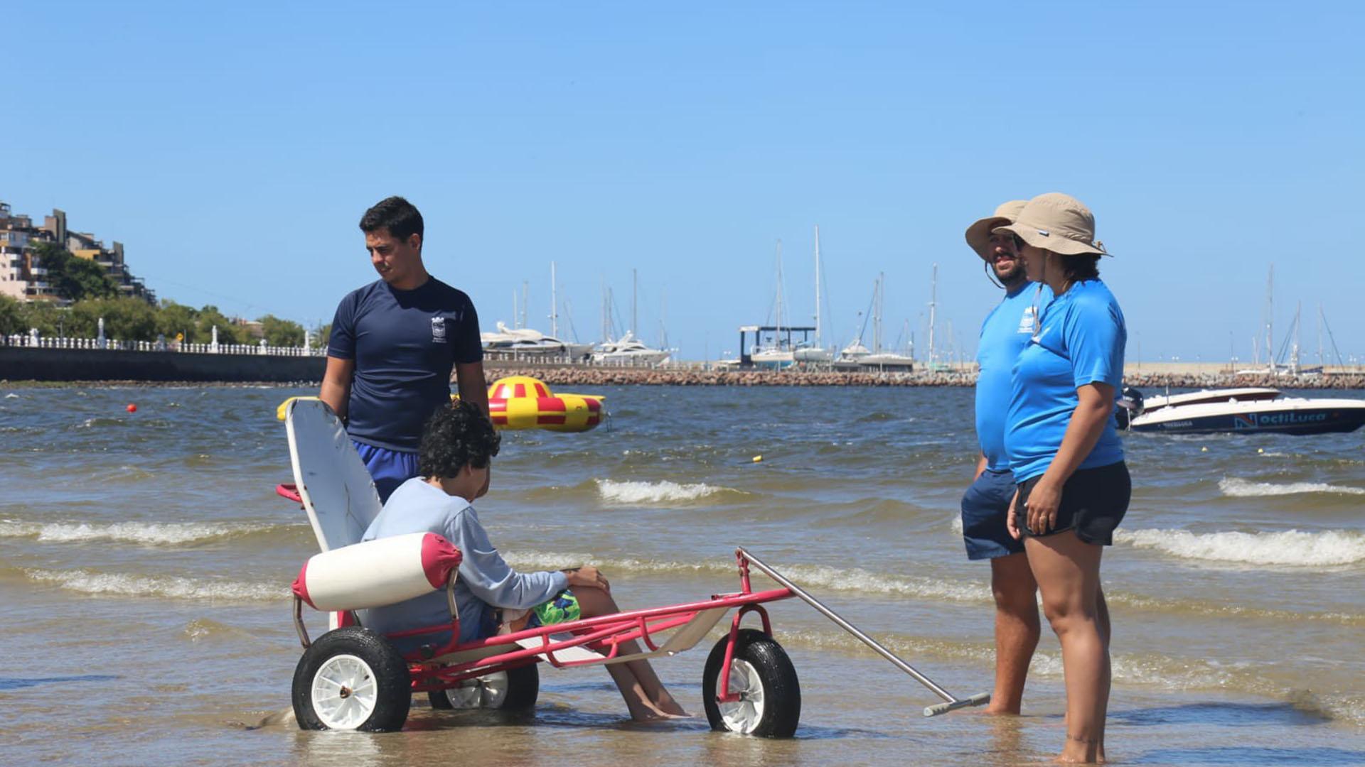 La silla, el joven y los profesionales encargados de llevarlo al agua: una postal de la playa inclusiva