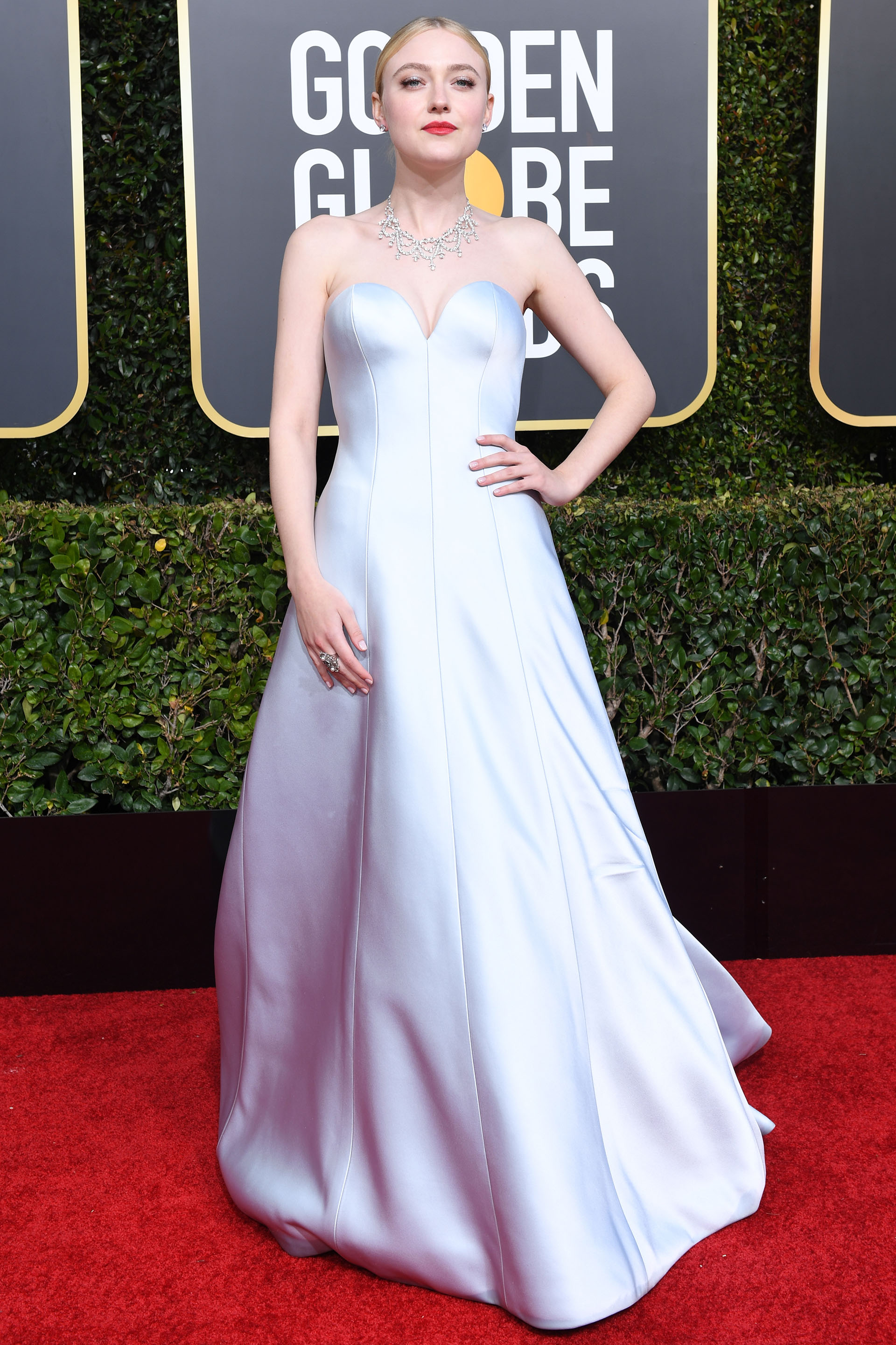Dakota Fanning impactó con su look en la red carpet de los Golden Globes con su total white look. Escote corazón y delicadas joyas de brillantes. ¿Su beauty look? Cabello tirante y labios colorados