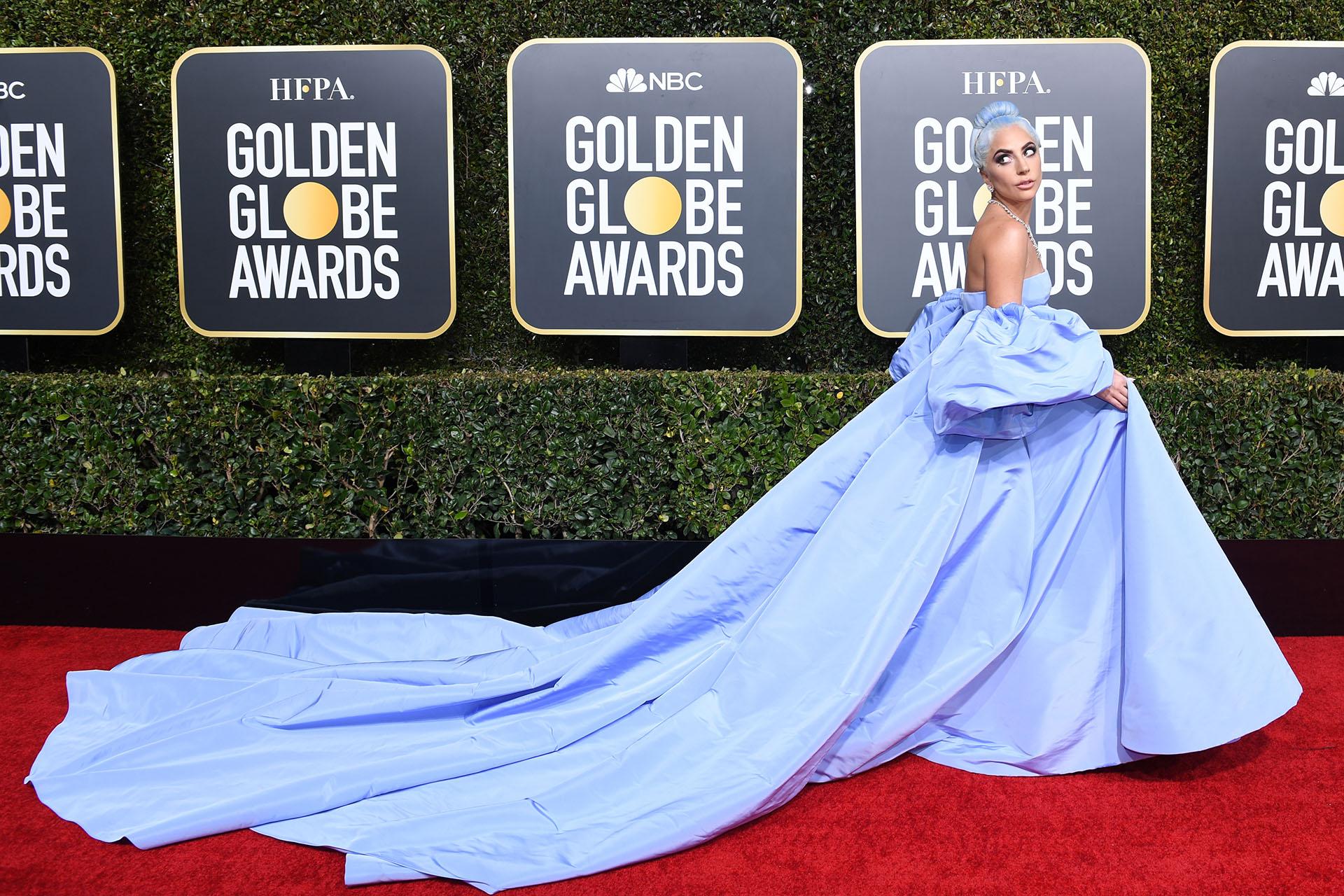 Lady Gaga nominada como mejor actriz, se lució en la red carpet de los Golden Globes con un voluptuoso e imponente vestido celeste. Con mangas acampanadas y escote strapless, acompañó los metros de cola del vestido con su cabello celeste