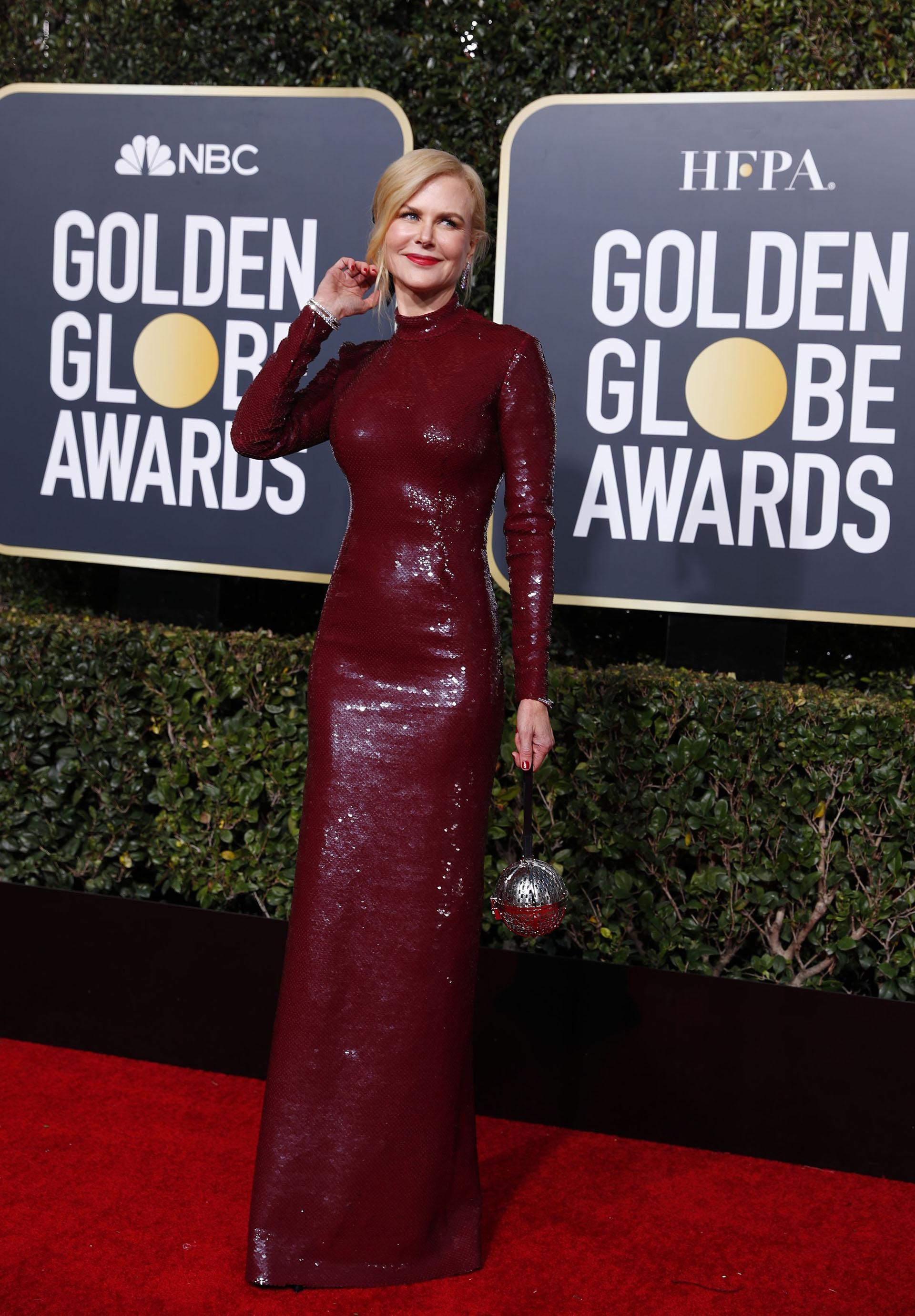 Paillettes y cuello cisne en color borravino. Nicole Kidman completó su look de red carpet con un clutch rígido en forma circular
