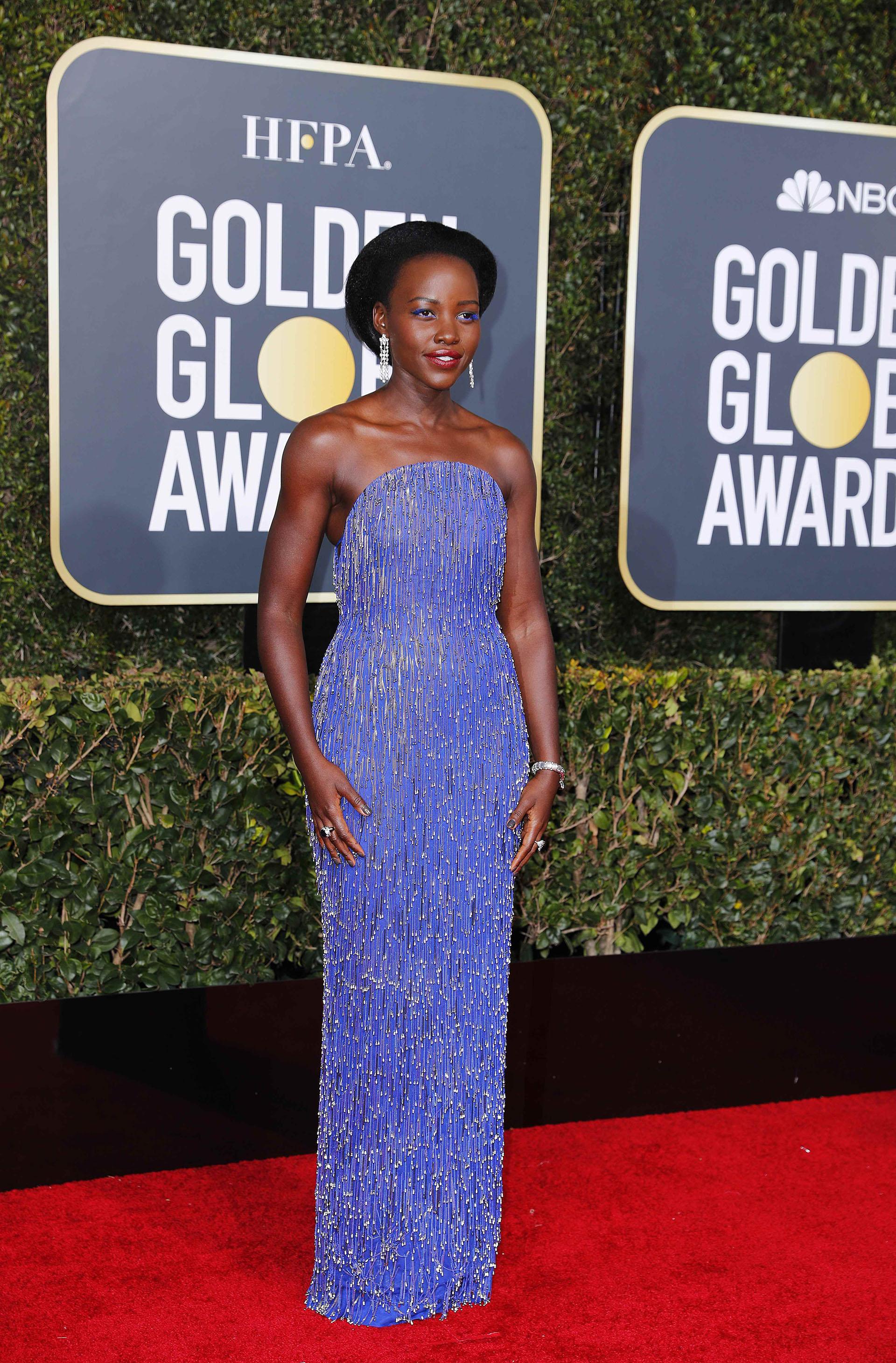 Lupita Nyong'o, al estilo charleston. Con un diseño strapless en azul marino completó su look con dos anillos, una esclava de brillantes y aros cascada