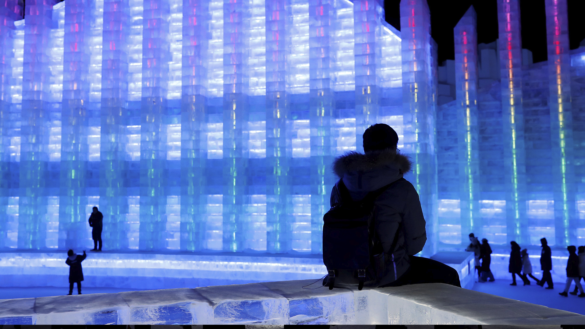 Un joven observa una enorme escultura de hielo en el festival de esculturas de hielo y nieve de Harbin