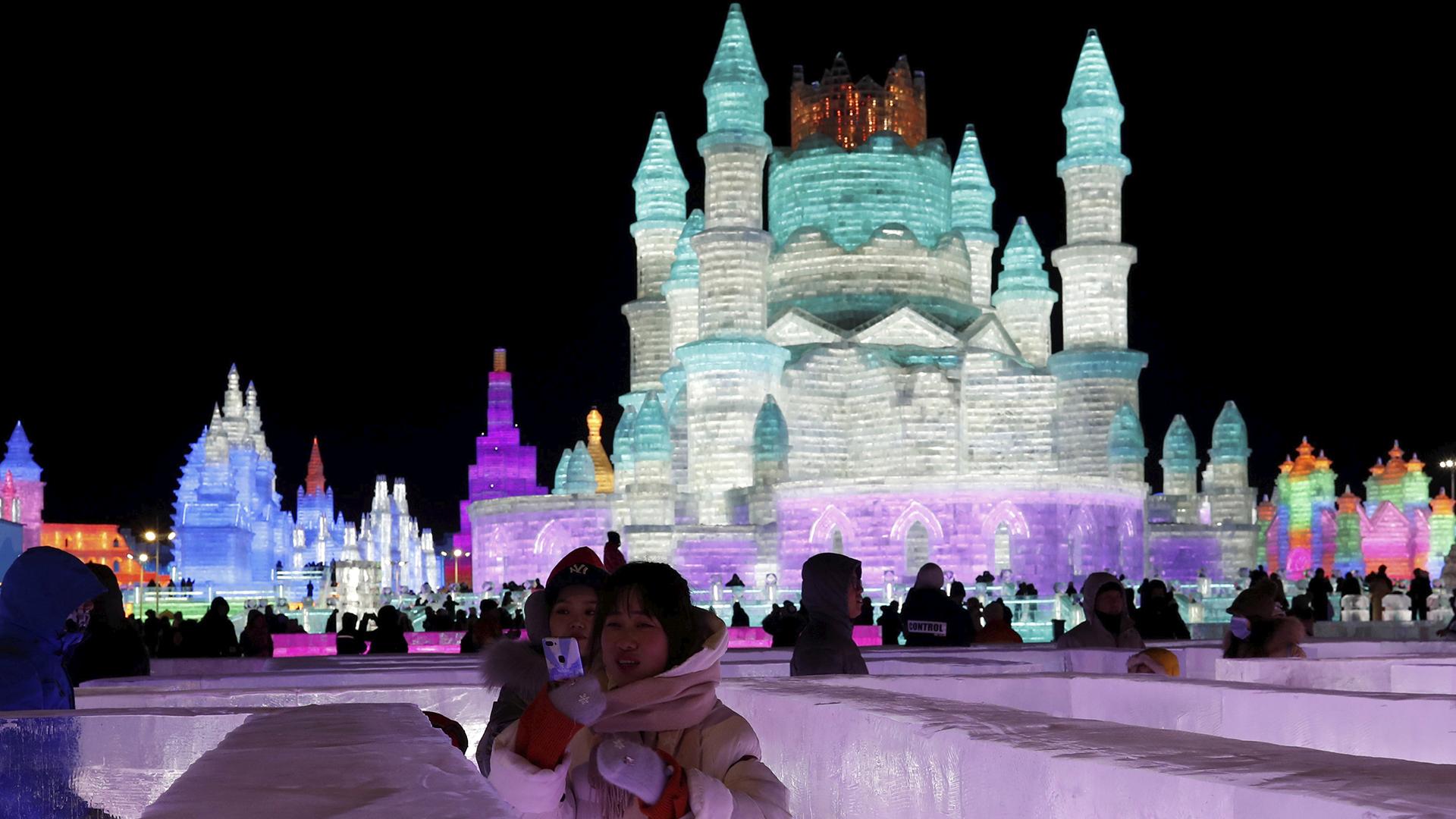 Una madre y su hija podan para una foto en frente de un castillo de hielo en Harbin