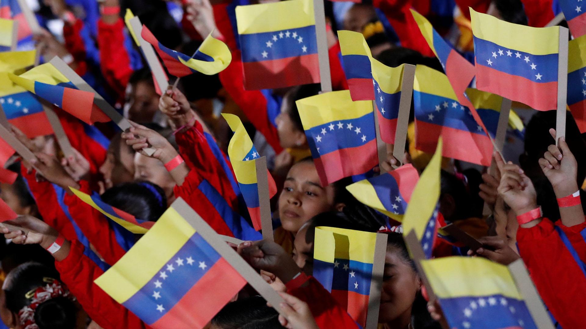 Un grupo de pequeños con banderas de Venezuela en el interior del TSJ (Reuters)