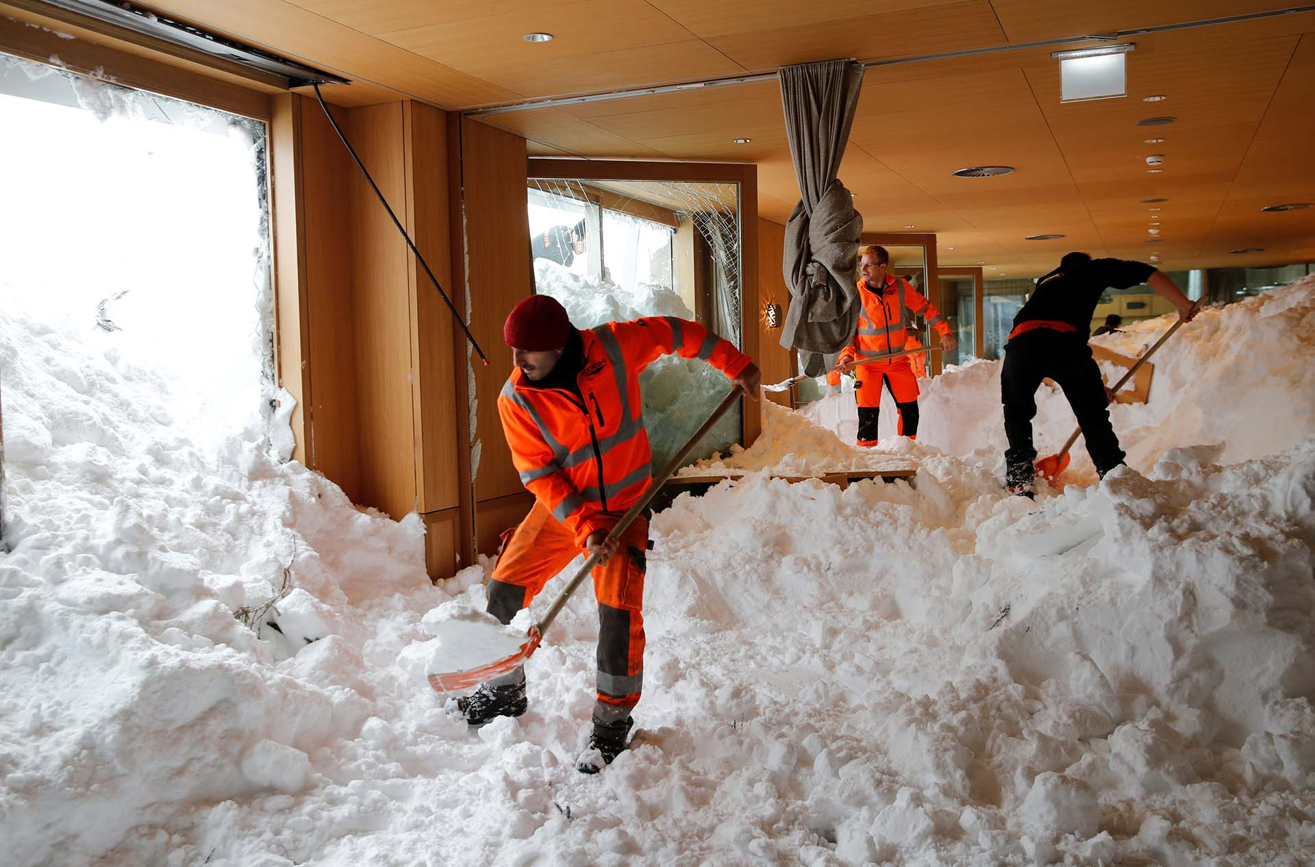 Trabajadores intentan remover la nieve de un restaurante tras una avalancha en Suiza (REUTERS/Arnd Wiegmann)