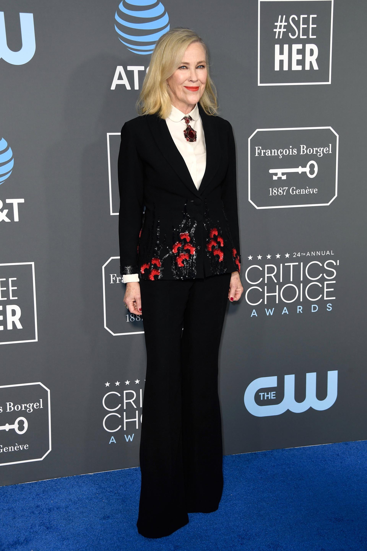 Catherine O'Hara apostó al traje masculino para los Critic's Choice Awards 2019. Pantalón oxford, y saco negro íntegramente bordado con flores y camisa blanca con detalle de colgante en el cuello