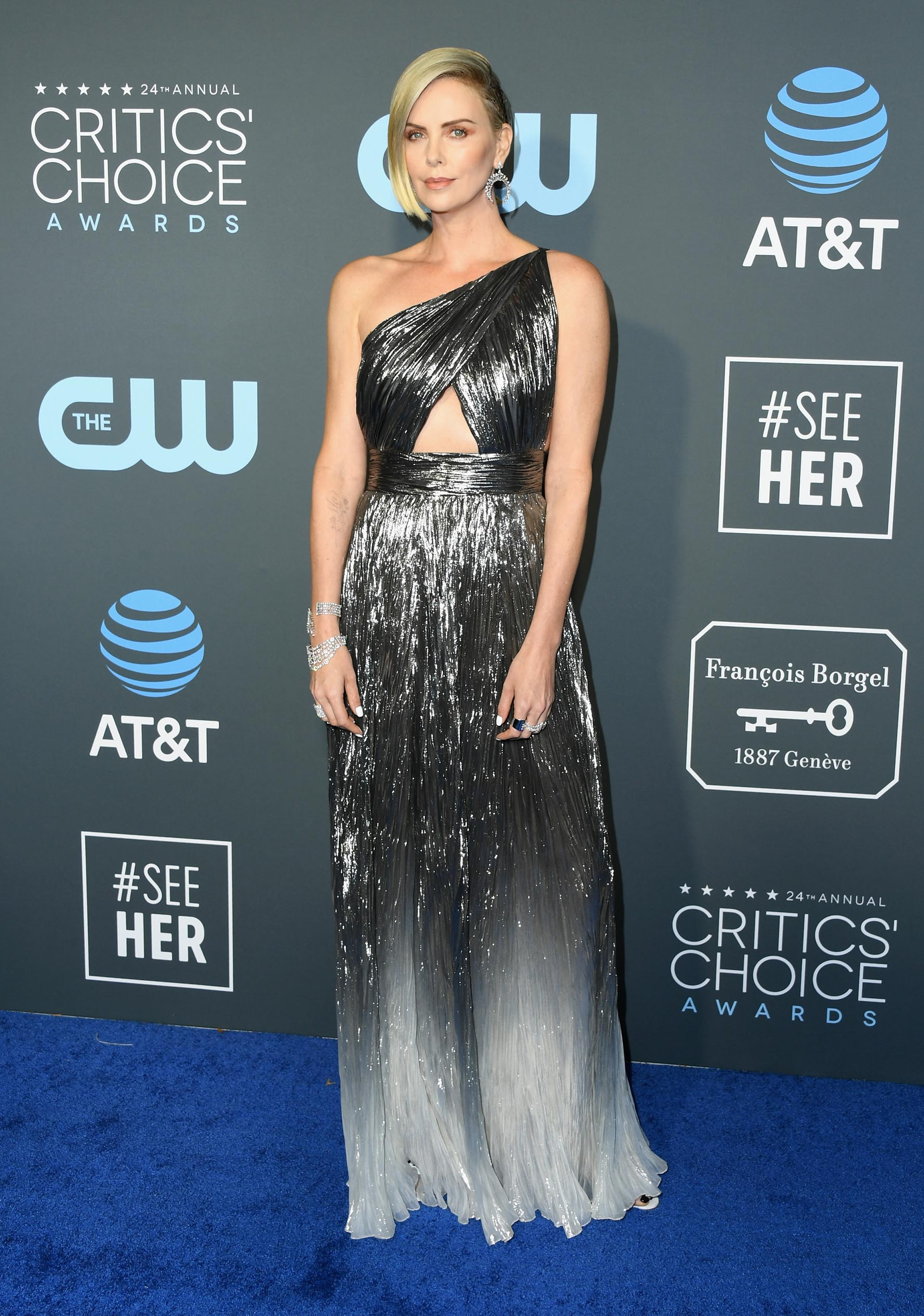 Charlize Theron vestida por Givenchy en degradés de metalizados. Drapeado, de corte asimétrico y un solo hombro, la actriz completó el look con esclavas y anillos de brillantes