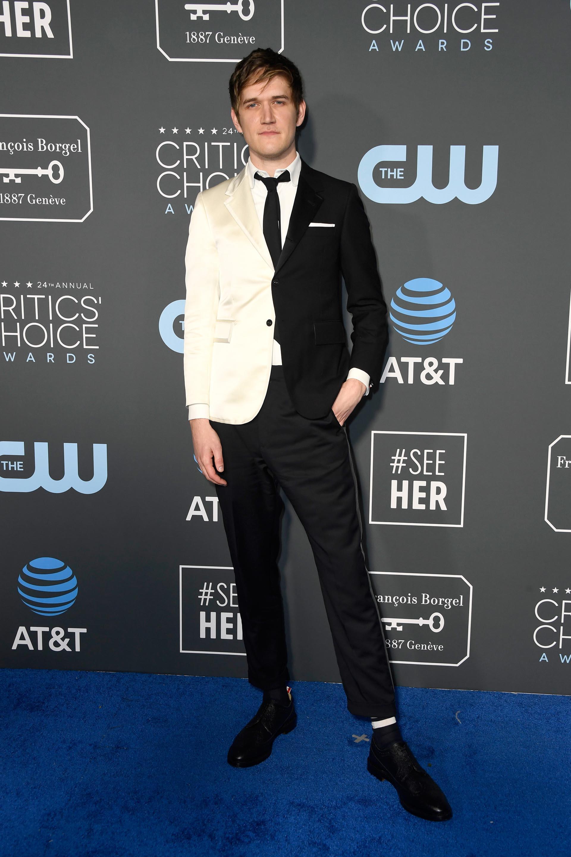 Bo Burnham lució un esmoquin con un saco bicolor en negro y blanco off white, camisa blanca, corbata slim en color negra, zapatos acordonados. ¿El detalle? medias de algodón y el pochette en el bolsillo del traje