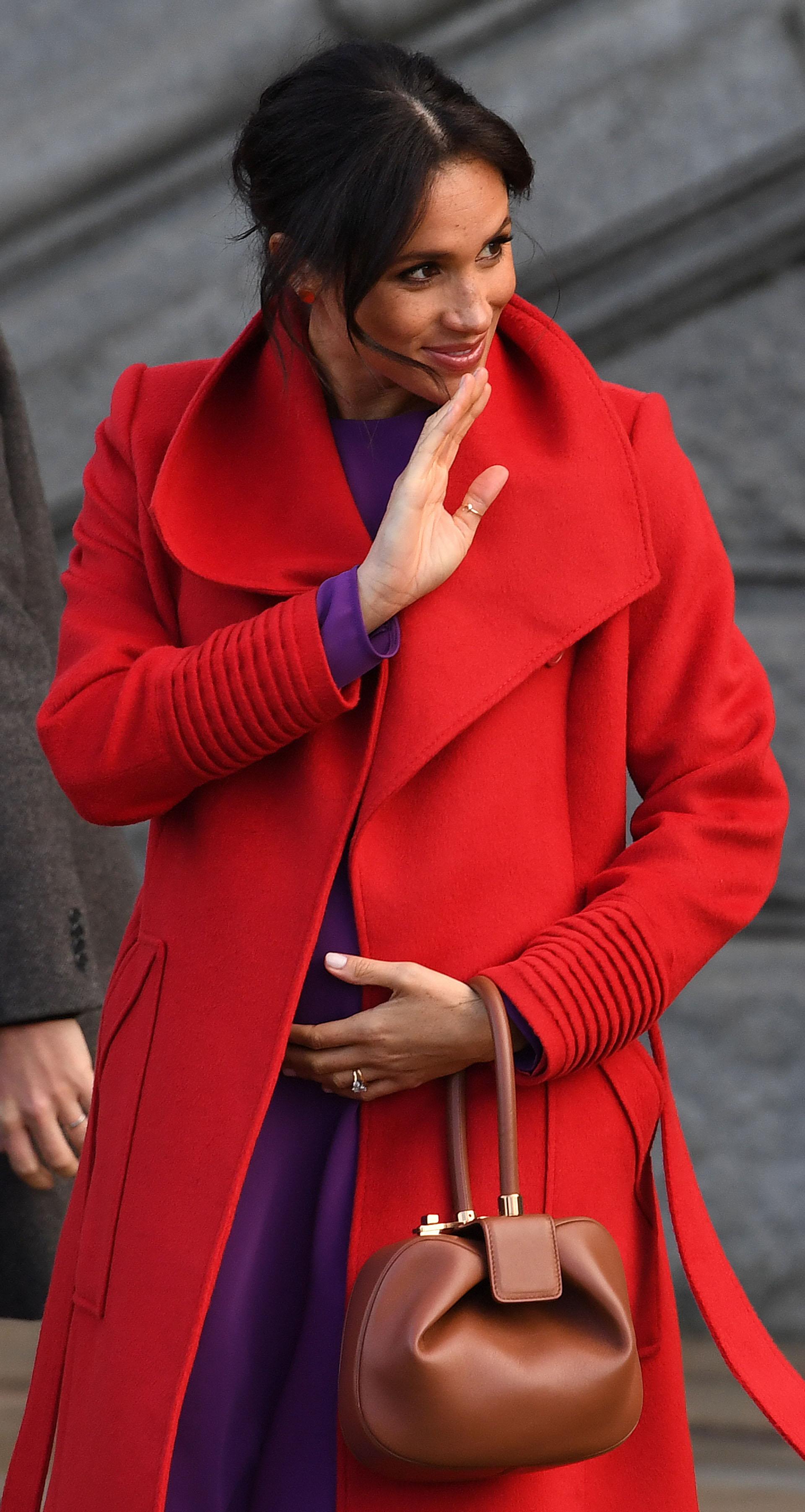 La duquesa de Sussex, lució su embarazo en la visita oficial al Birkenhead junto al príncipe Harry, y optó por un vestido violeta low cost de 50 dólares y un tapado rojo de Sentaler. Su look color block recordó mucho a dos outfits del mismo tono usados por la mamá del príncipe Harry (AFP)