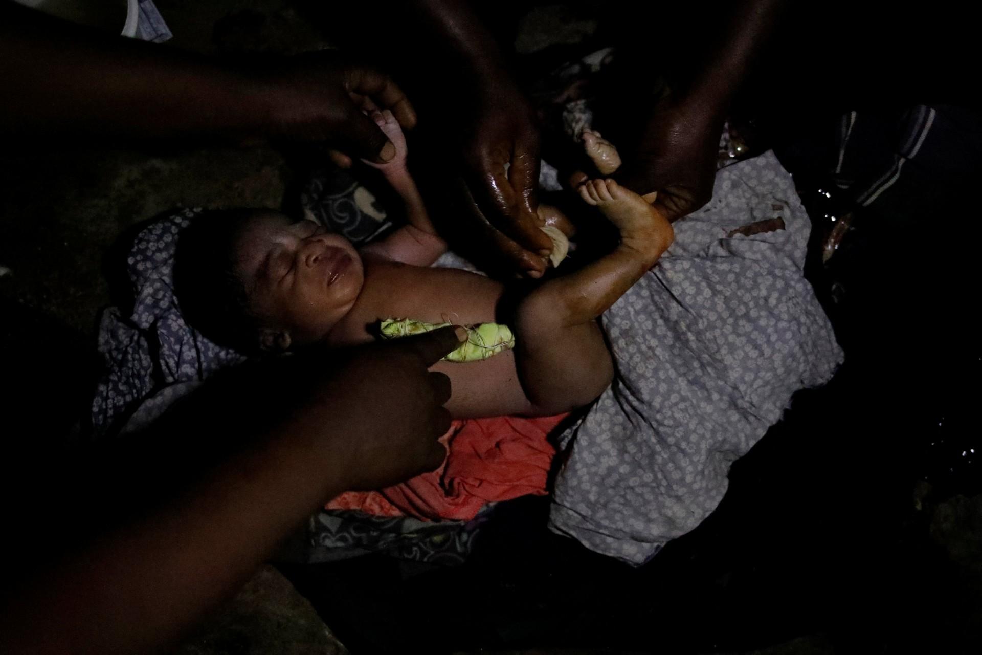 Una vecina y un familiar cuidan a la recién nacida Rebeca en su casa en Boucan Ferdinand, Haití, el 8 de octubre de 2018.