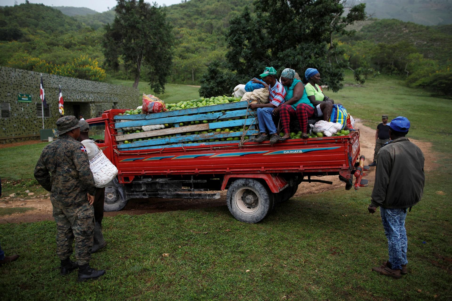 Un miembro de las Fuerzas Armadas Dominicanas mira un camión cargado con aguacates y viajeros en la frontera entre República Dominicana y Haití, en el puesto militar de El Guacate, provincia de Independencia, República Dominicana, 2 de octubre de 2018.