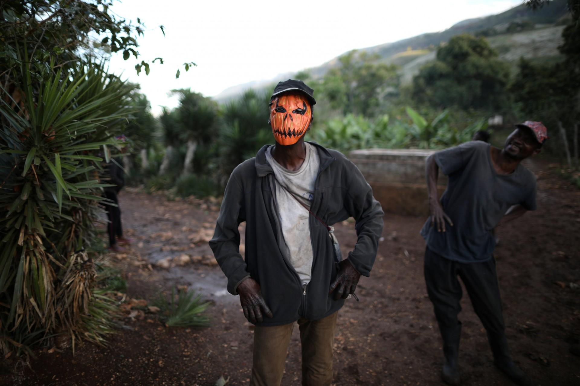 Un hombre sordo se detiene usando una máscara de calabaza en una calle en Boucan Ferdinand, Haití, 7 de abril de 2018.