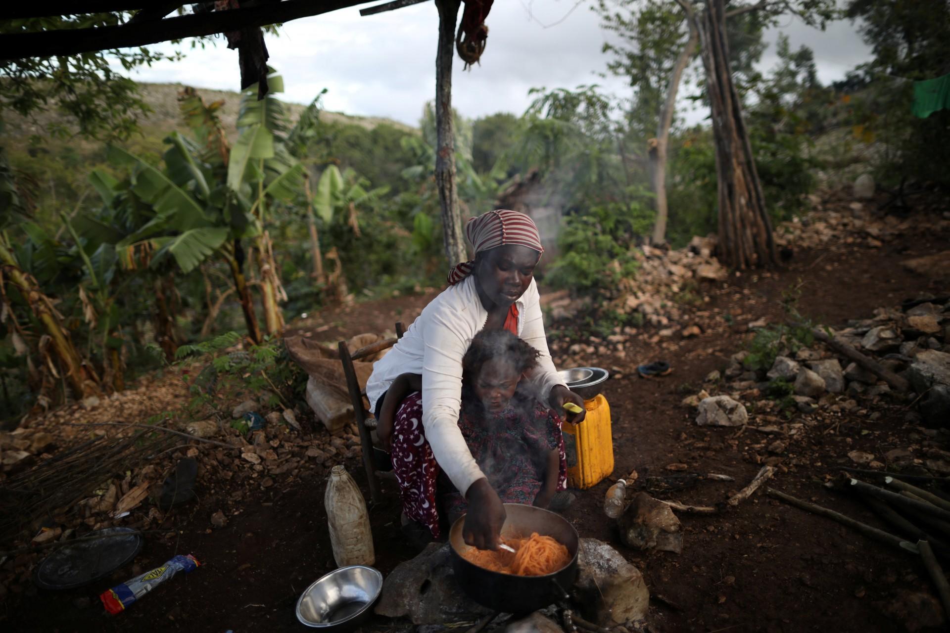 Tipiti cocina pasta mientras peina el cabello de su hija en Boucan Ferdinand, Haití, el 8 de abril de 2018.
