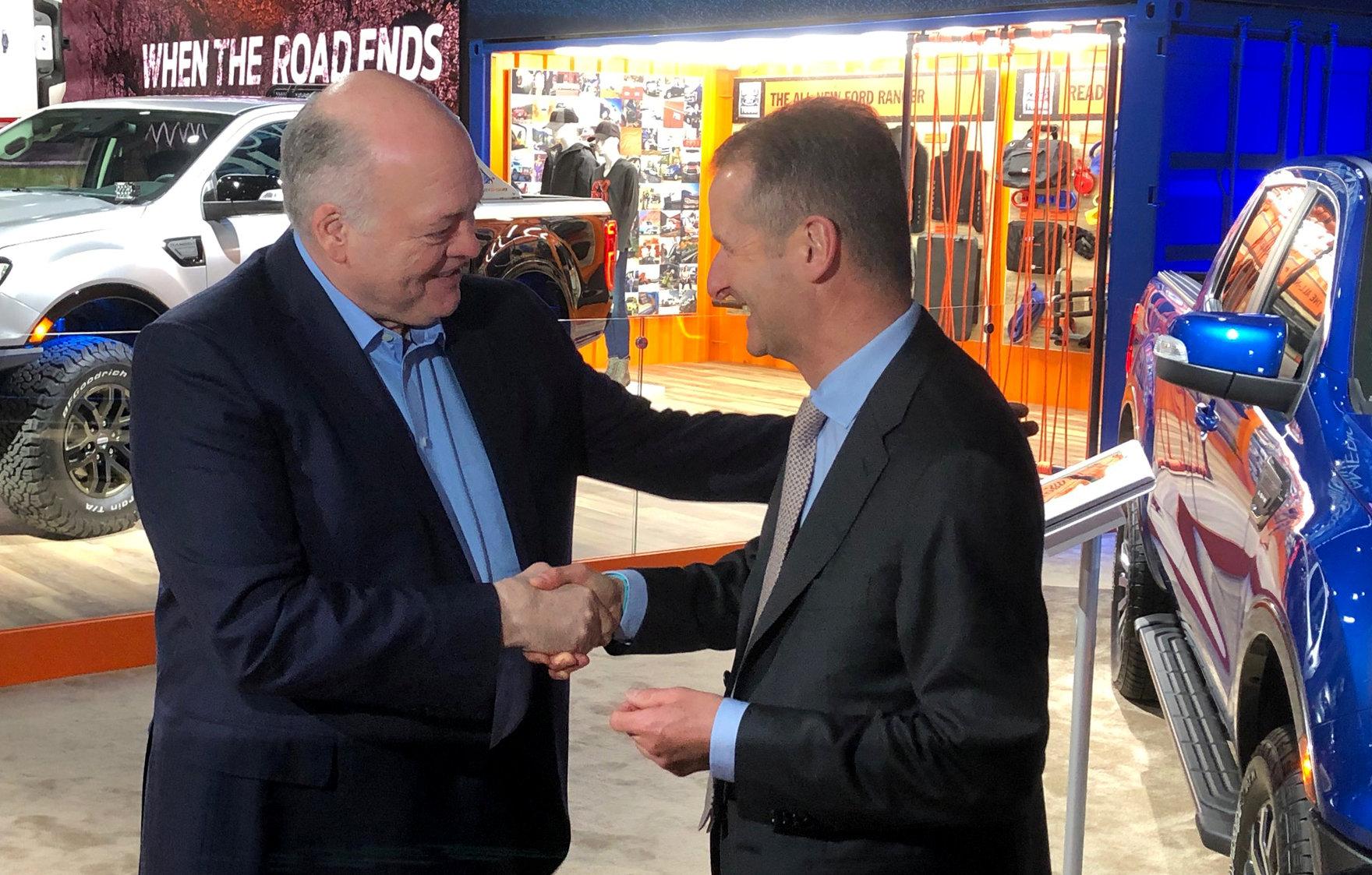 El CEO de Ford, Jim Hackett, estrecha la mano del líder de Volkswagen, Herbert Diess (Reuters)