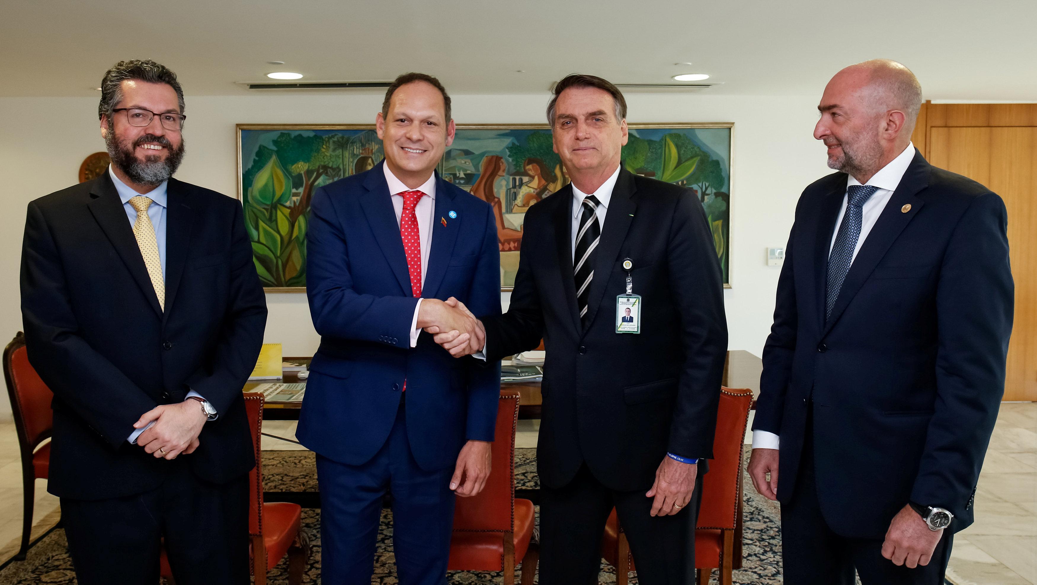 Jair Bolsonaro estrecha la mano del presidente del Tribunal Supremo venezolano en el exilio Miguel Angel Martin, junto al canciller Ernesto Araujo (izquierda) y al representante de la OEA Gustavo Cinosi durante su encuentro en Brasilia (Alan Santos/Presidencia de Brasil via Reuters)