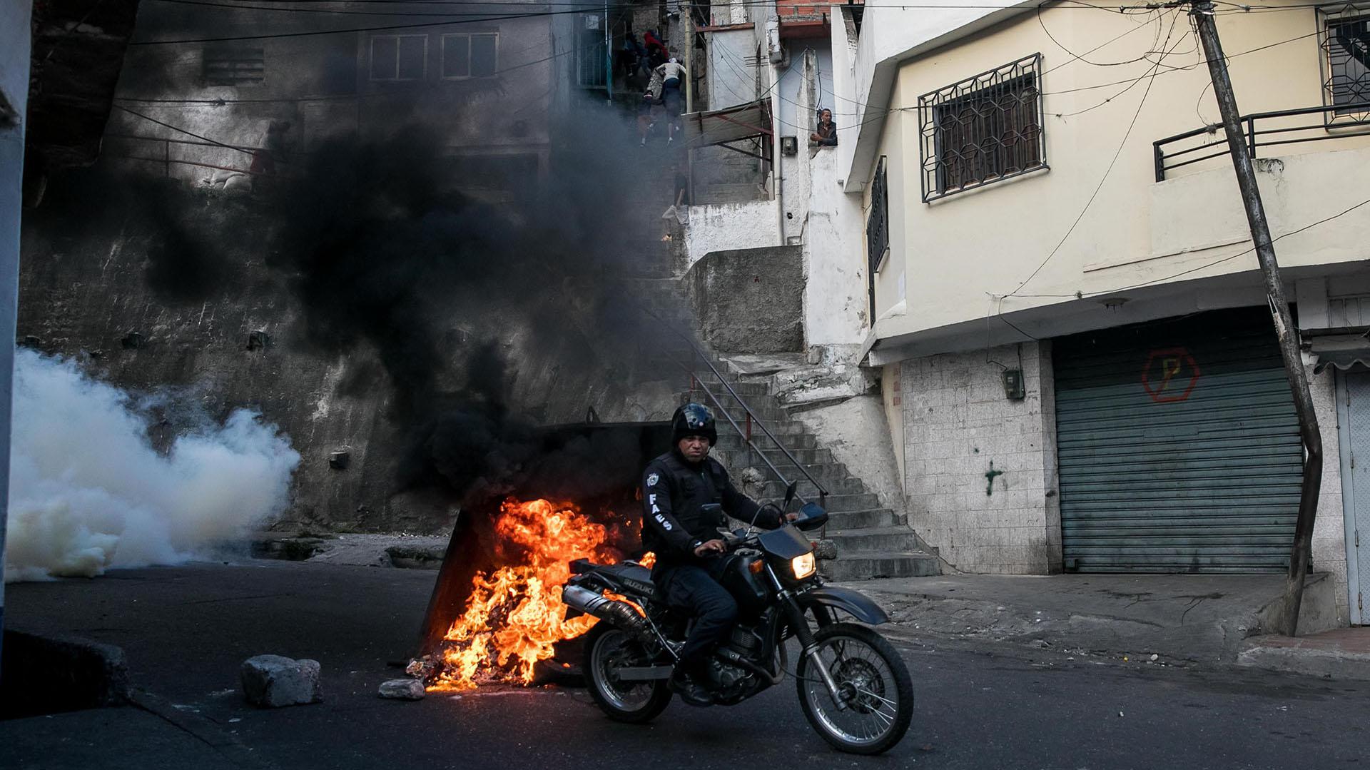 Un miembro de Fuerzas de Acciones Especiales (FAES) se moviliza en su motocerca a la manifestación