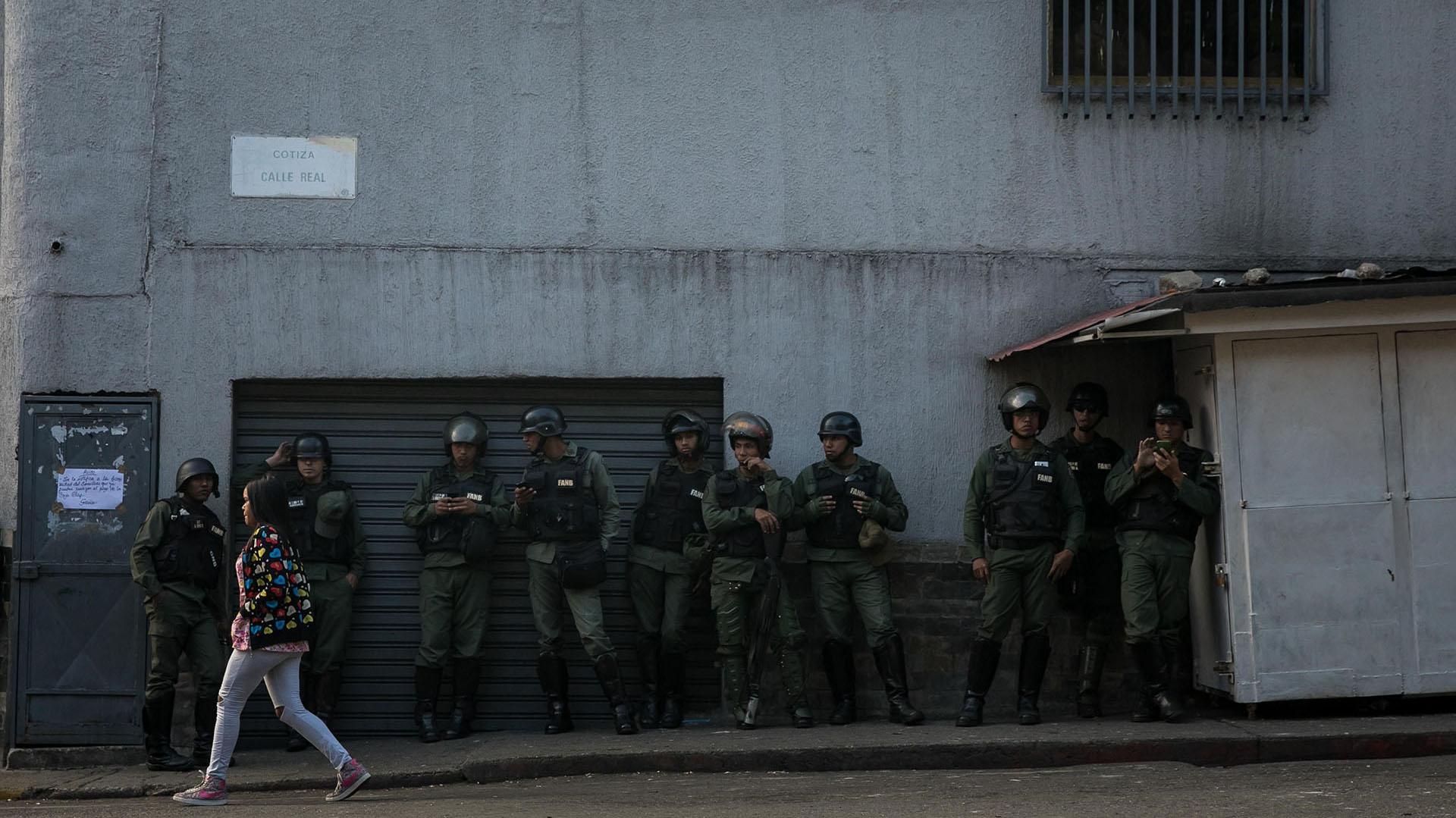 Miembros de la Guardia Nacional Bolivariana (GNB) aguardan en una pared mientras un grupo de personas se manifiestan en una calle