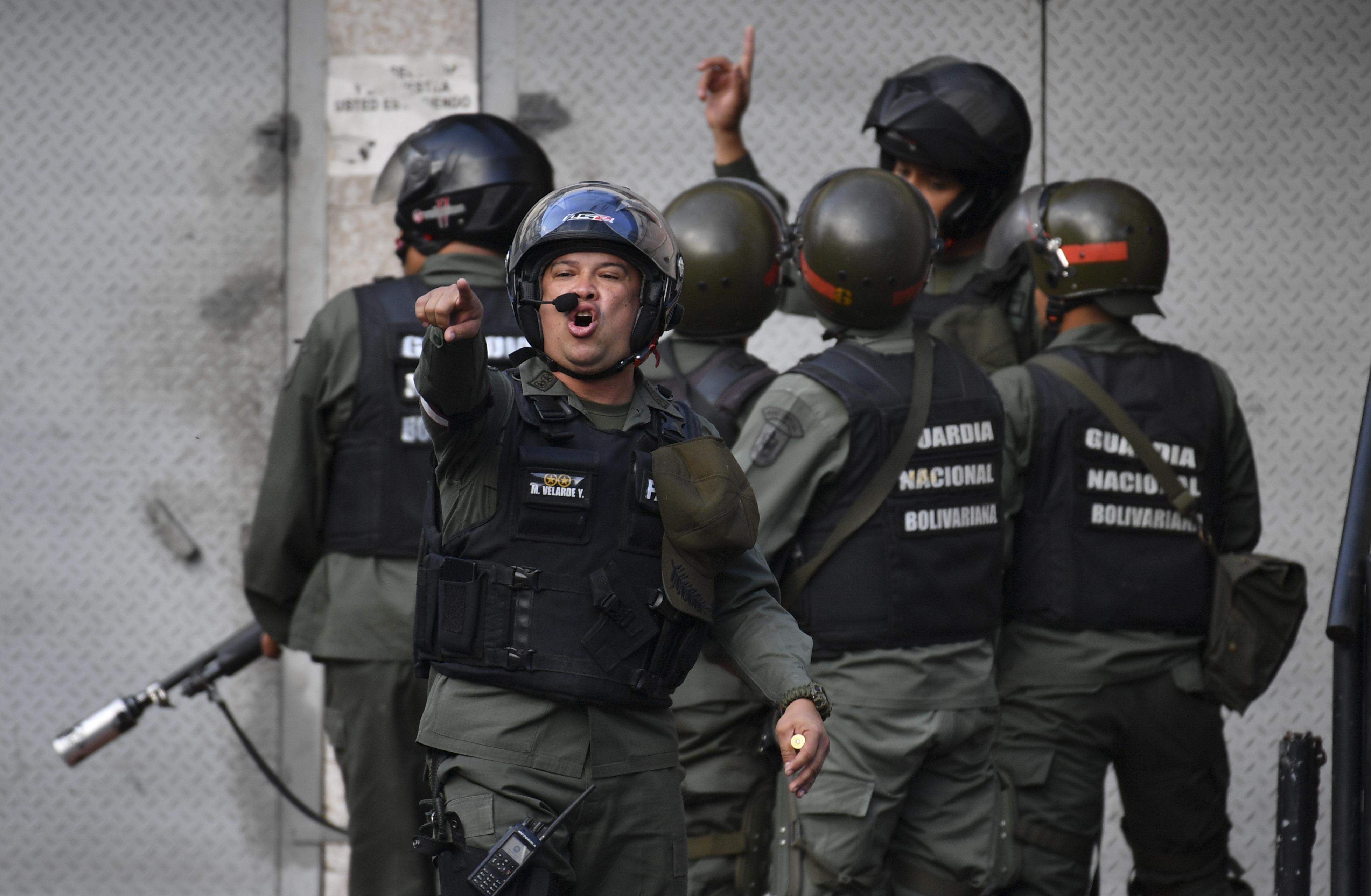 Los agentes de la GNB lanzan advertencias a los manifestantescerca del cuartel de Cotiza, en Caracas