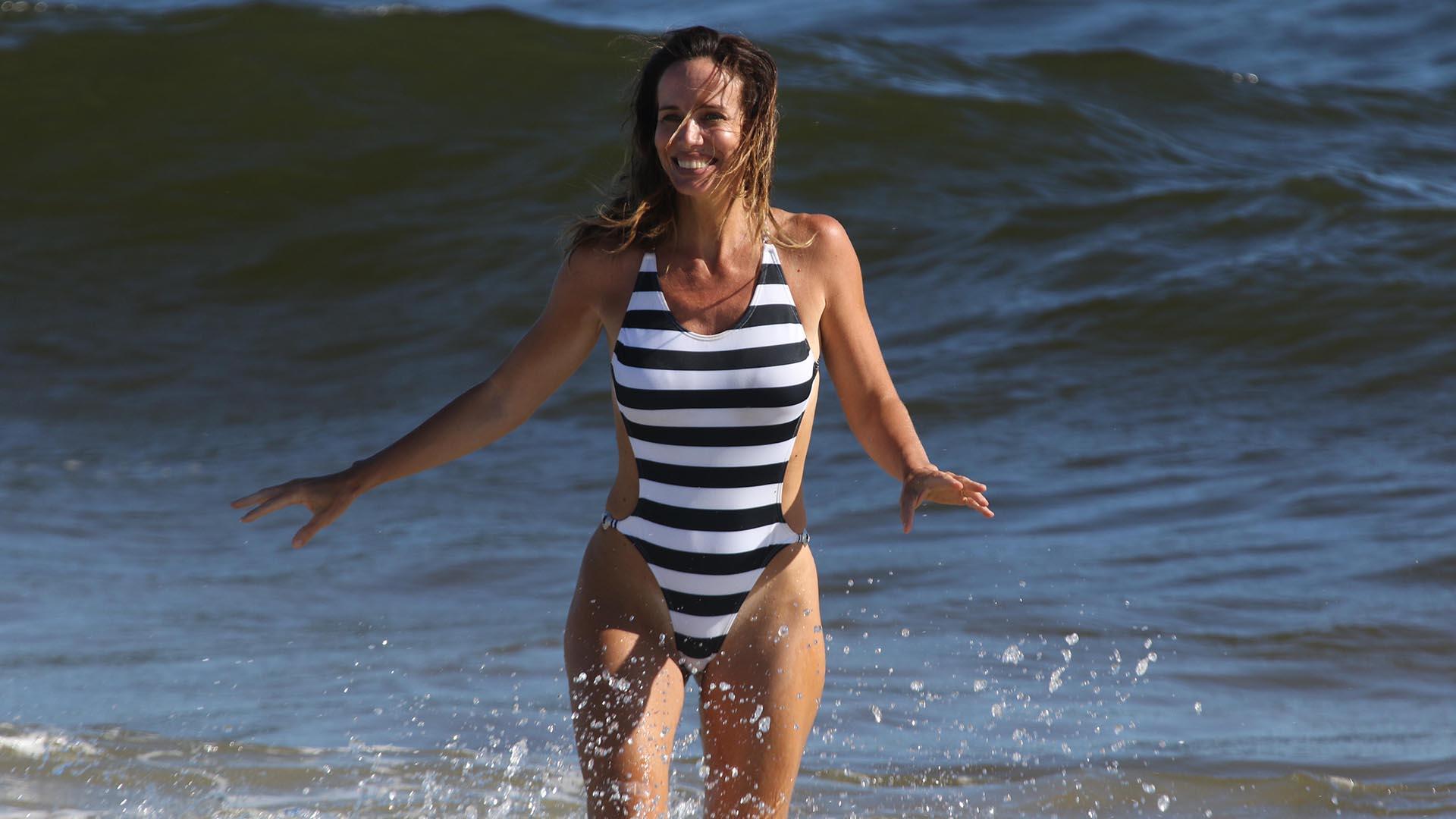 Carolina Pratt disfrutó del mar durante sus vacaciones en Uruguay. La esposa de Guillermo Andino llevaba todo su cuerpo en un traje de baño a rayas en pleno crecimiento (GM Press)