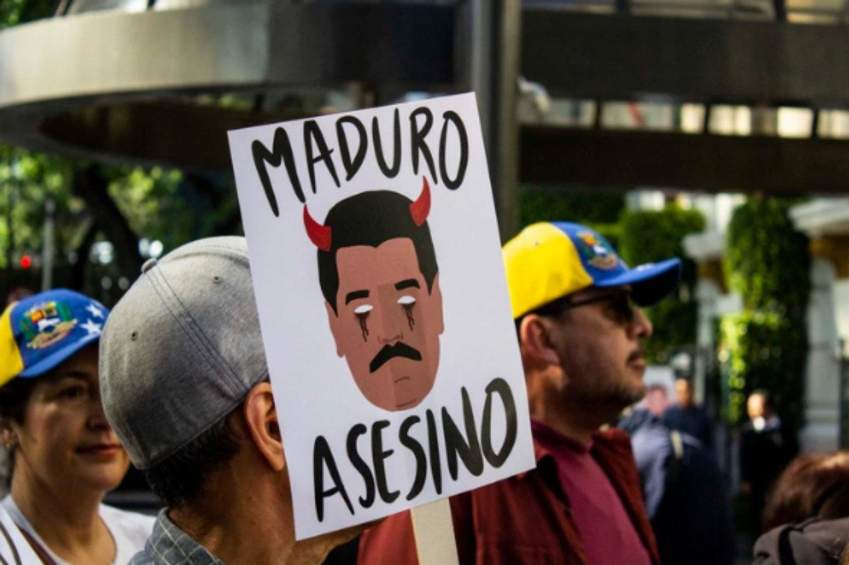 """Un hombre sosteniendo un cartel con la leyenda """"Maduro Asesino"""" (Foto: Gibrán Casas)"""