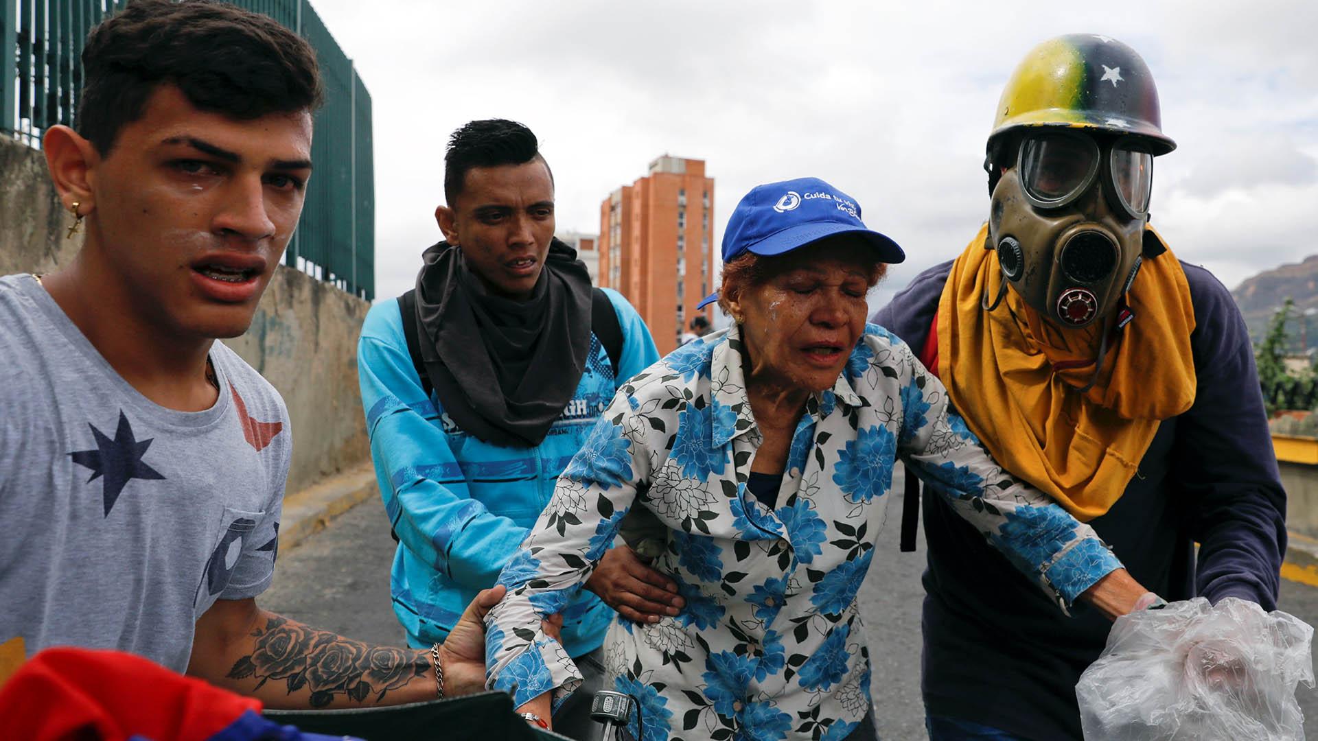 Una mujer es socorrida por manifestantes, ante los gases lacrimógenos lanzados por los uniformados