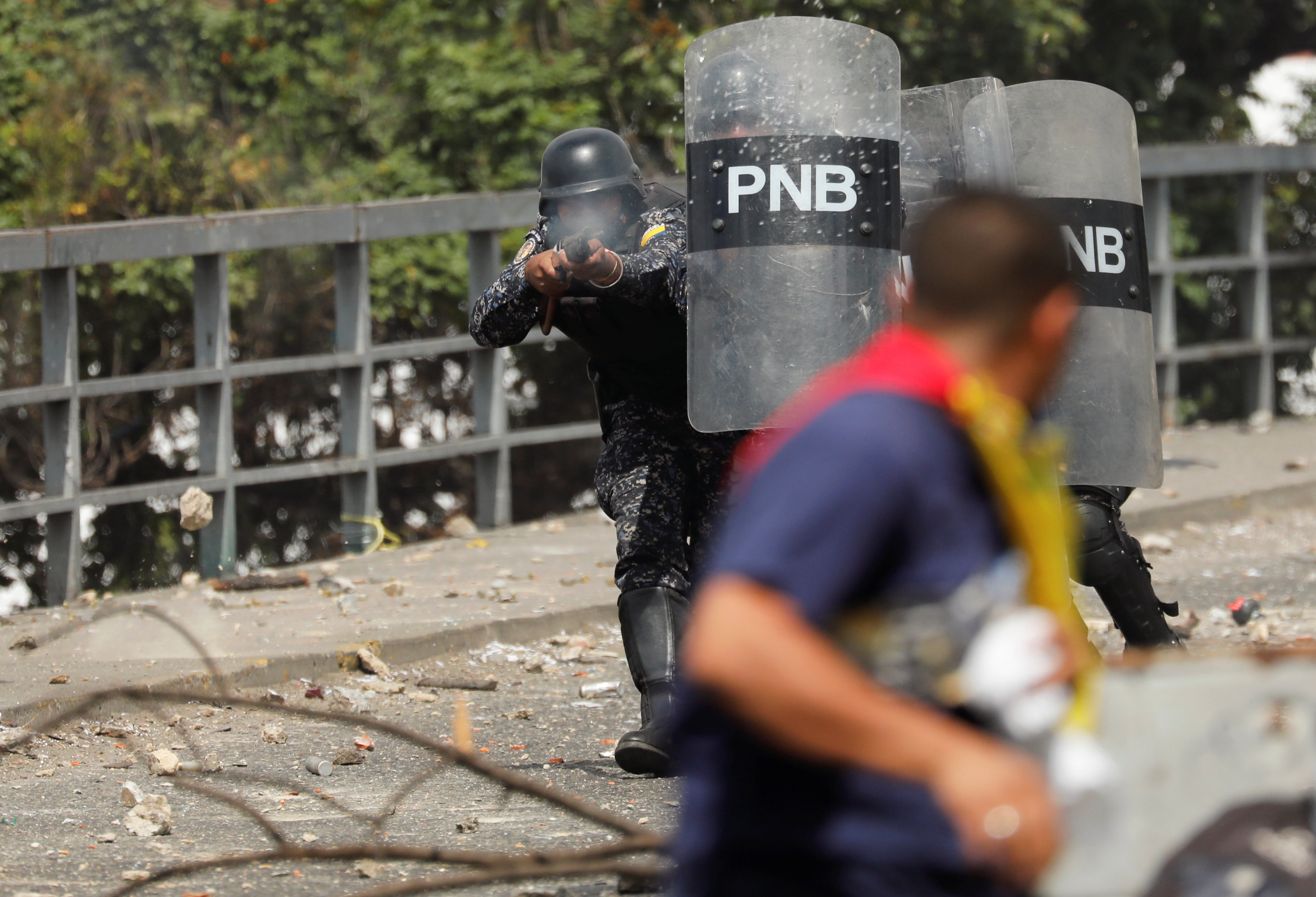 Un miembro de la Policía Nacional Bolivariana dispara balas de goma a los manifestantes en Caracas