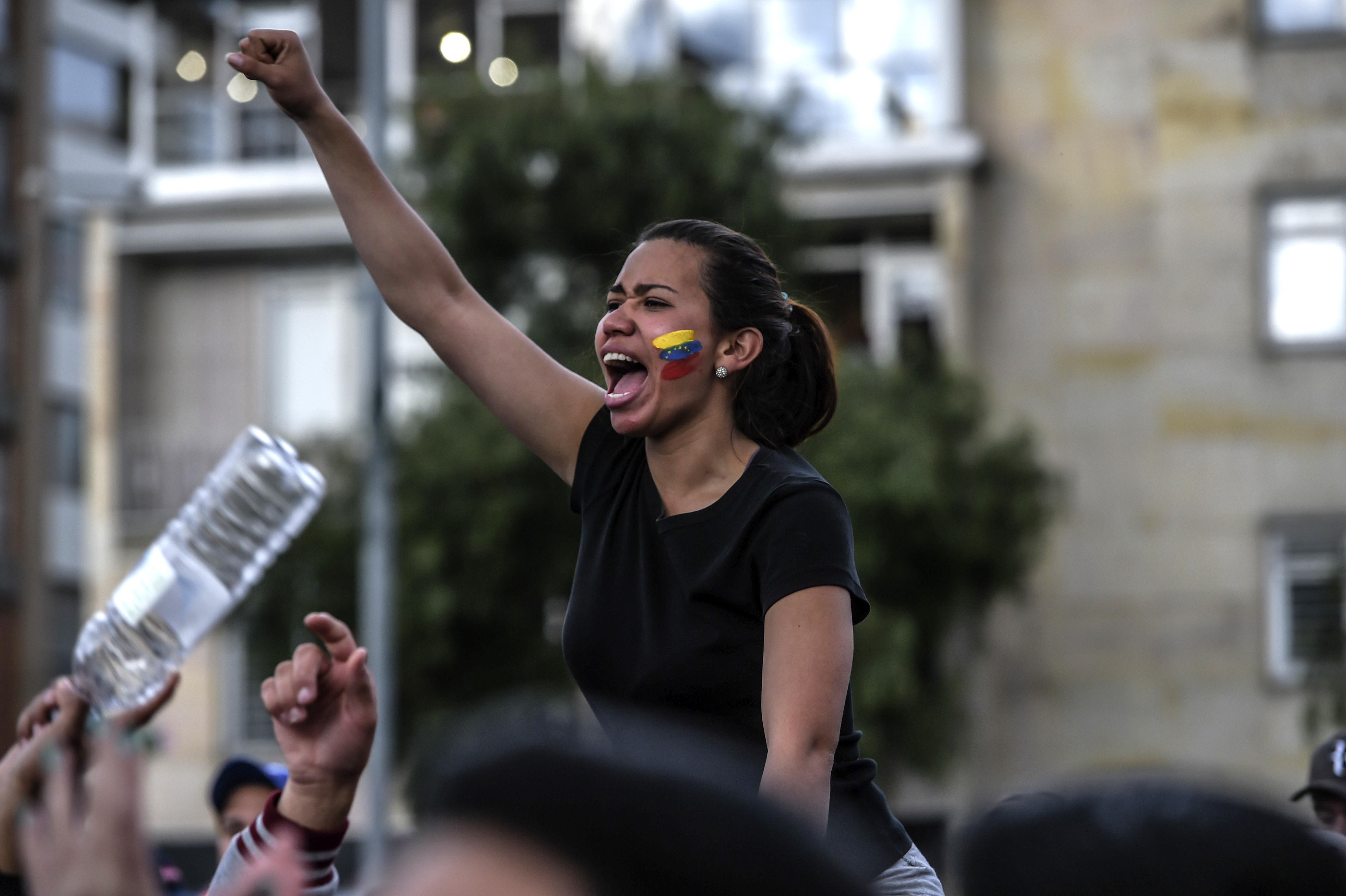 Un joven venezolana protesta contra la dictadura chavista en Bogotá. (Photo by Juan BARRETO / AFP)