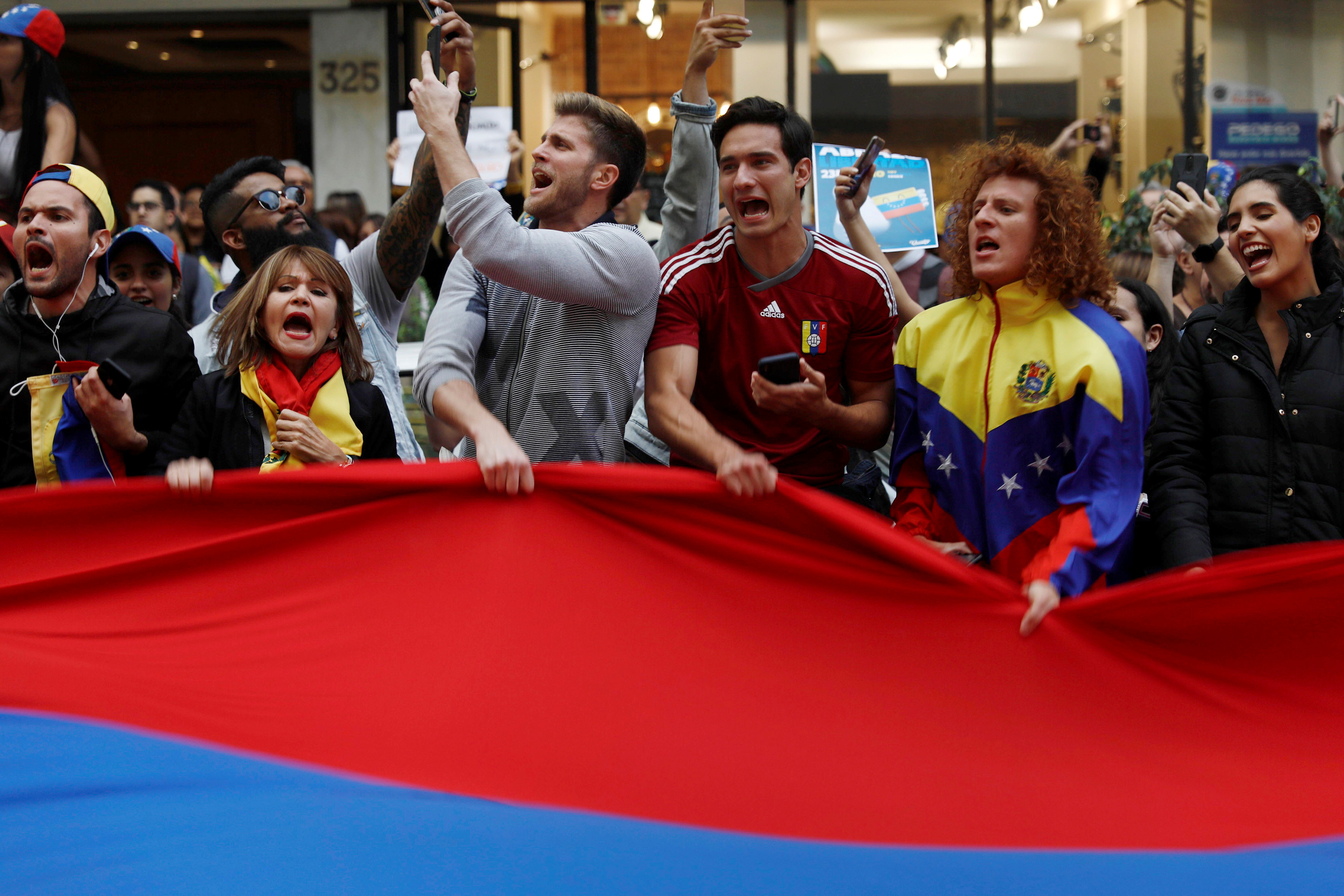 People hold a Venezuelan flag as they gather in support of Venezuela's opposition leader Juan Guaido outside the Embassy of Venezuela in Mexico City, Mexico January 23, 2019. REUTERS/Edgard Garrido