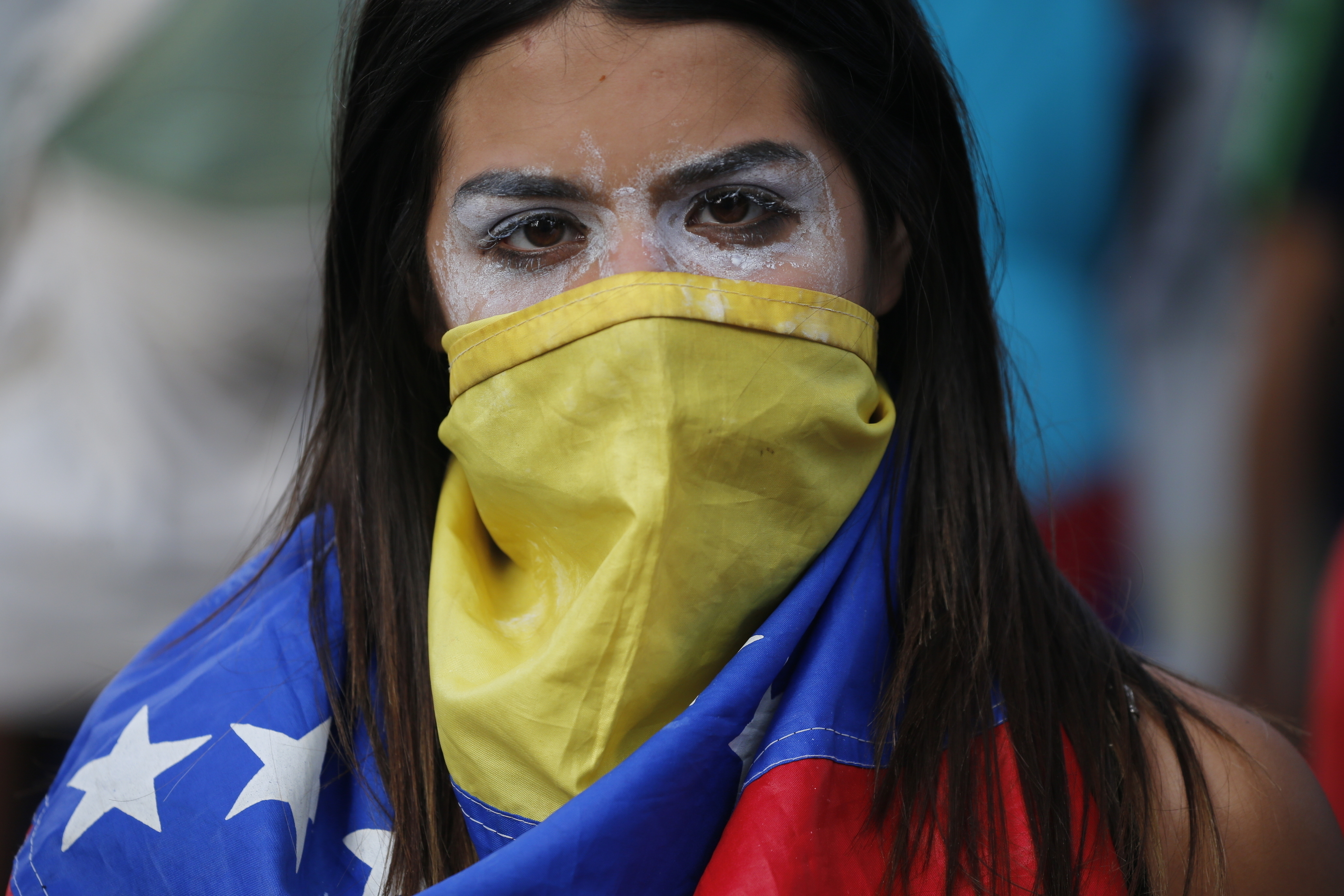 Una manifestante antigubernamental, con la cara tapada por una bandera de Venezuela y pasta dentífrica alrededor de los ojos para mitigar el efecto de los gases lacrimógenos, durante enfrentamiento con las fuerzas de seguridad tras una protesta para exigir la renuncia del presidente del país, Nicolás Maduro, en Caracas, Venezuela, el 23 de enero de 2019. (AP Foto/Fernando Llano)