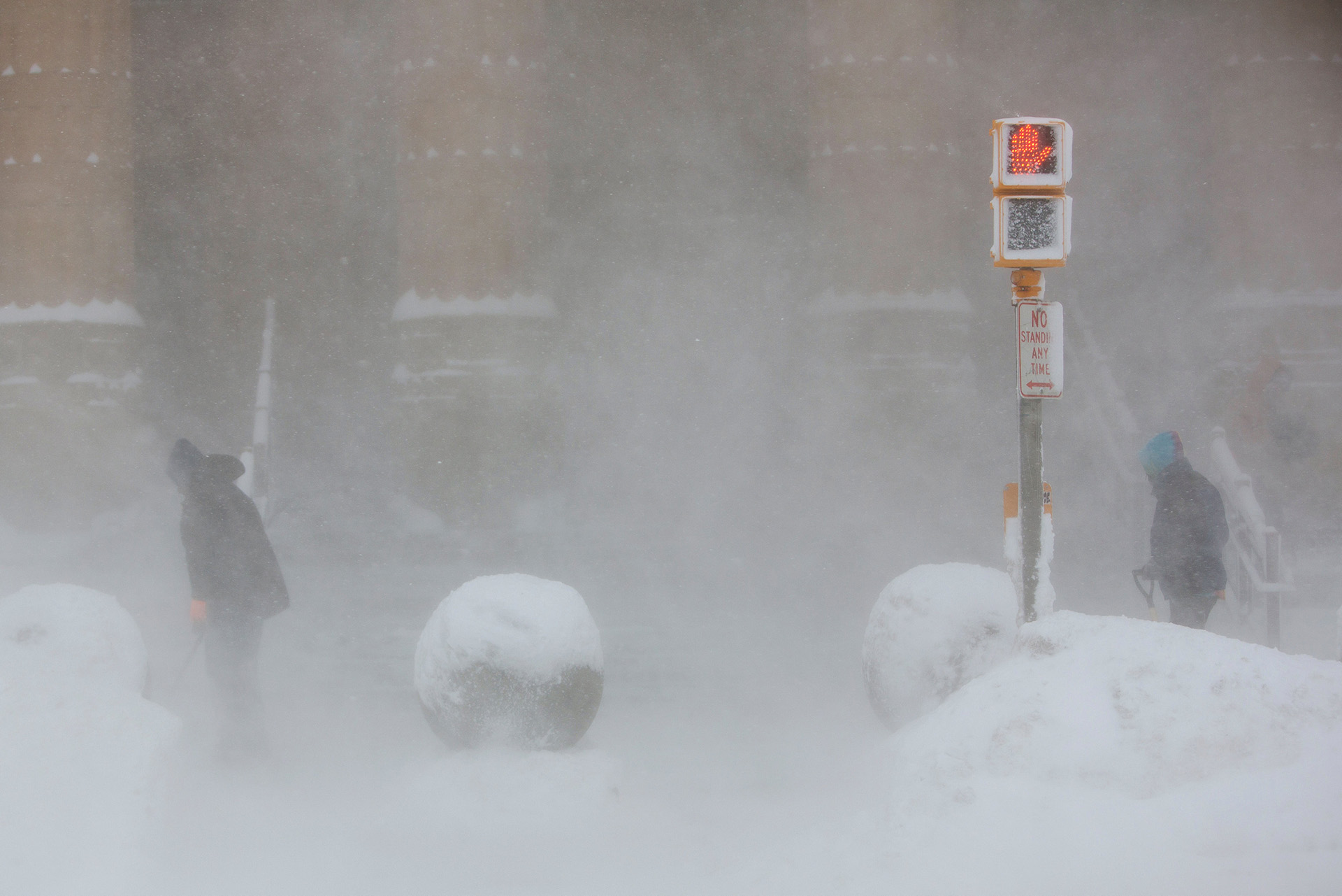Trabajadores tratan de despejar la entrada al Ayuntamiento de Buffalo, en medio de una tormenta de nieve.