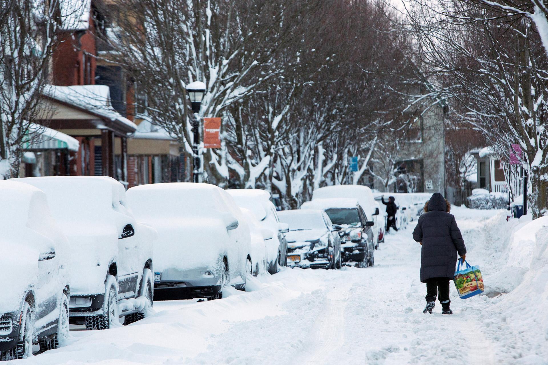 Una mujer camina por una calle de Buffalo, donde ha acumulado la nieve.