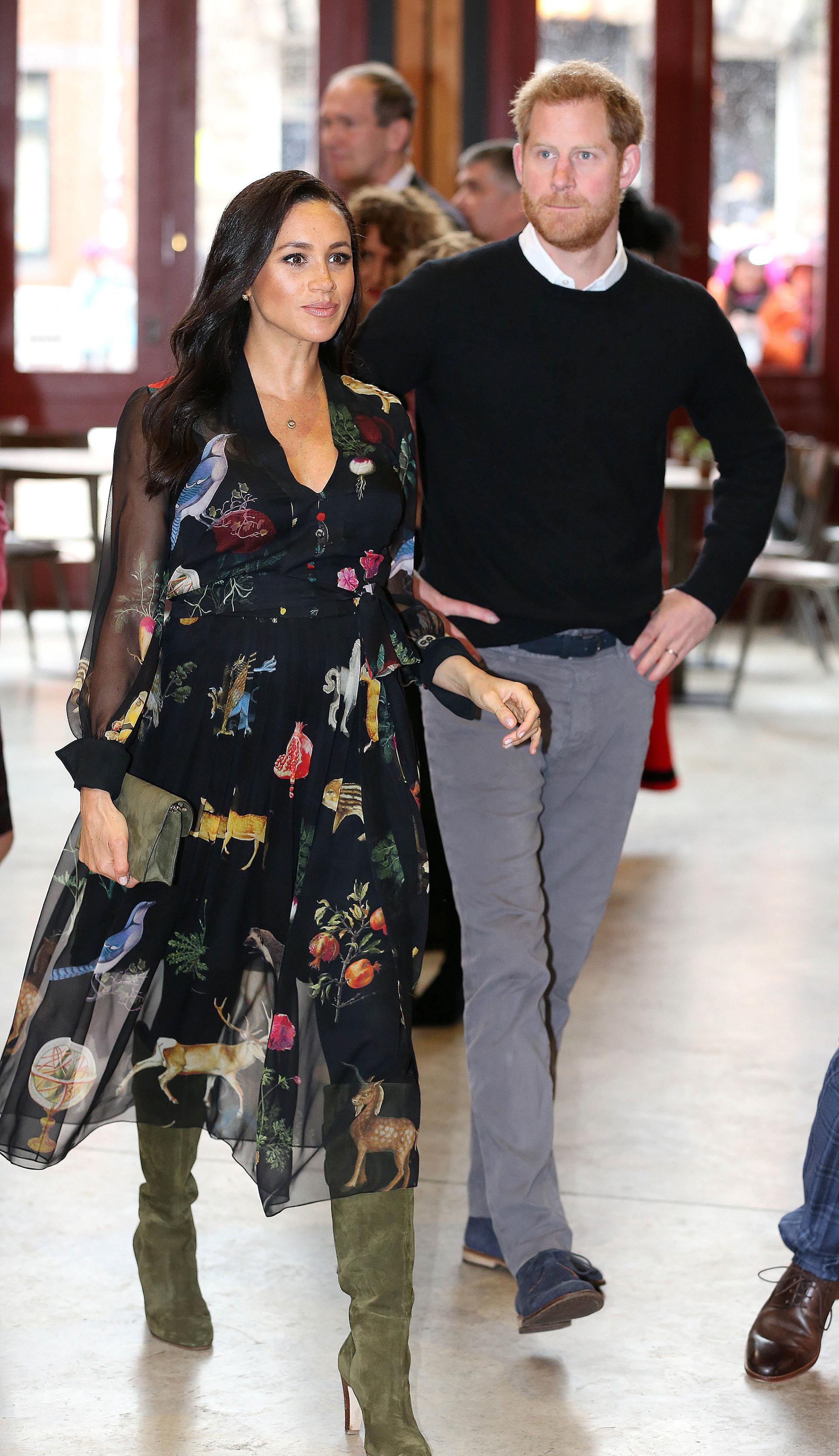 El día que visitó Bristol con el Príncipe Harry, la duquesa optó por combinar un vestido estampado de Oscar de la Renta con un sobre y botas verde oliva de Sarah Flint (REUTERS)