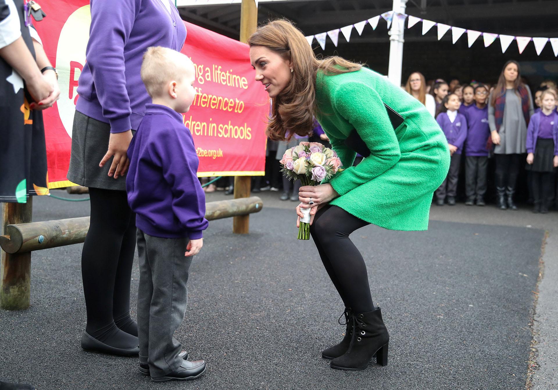 La duquesa de Cambridge hablando con uno de los niños de la escuela