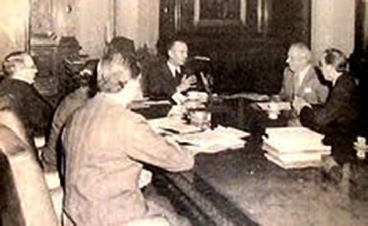 Luis Cerruti Costa (al fondo) de saco negro y anteojos, el presidente de facto Lonardi (en la cabecera de la mesa), Luis Natalini, secretario general del gremio de Luz y Fuerza, y a Andrés Framini, titular de la Asociación Obrera Textil