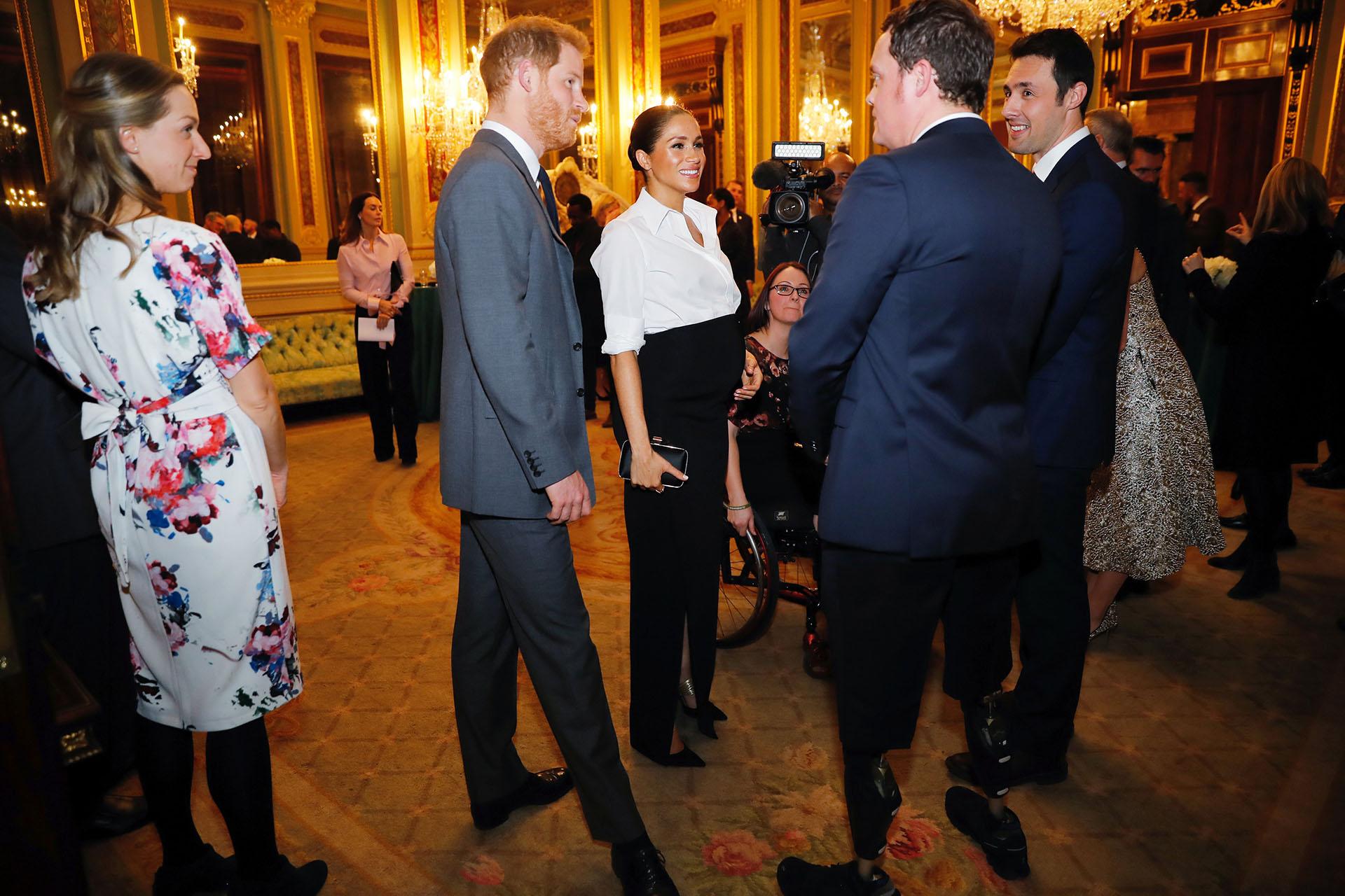 Acompañada por su marido, el príncipe Harry, la pareja habló animadamente con los invitados a la recepción
