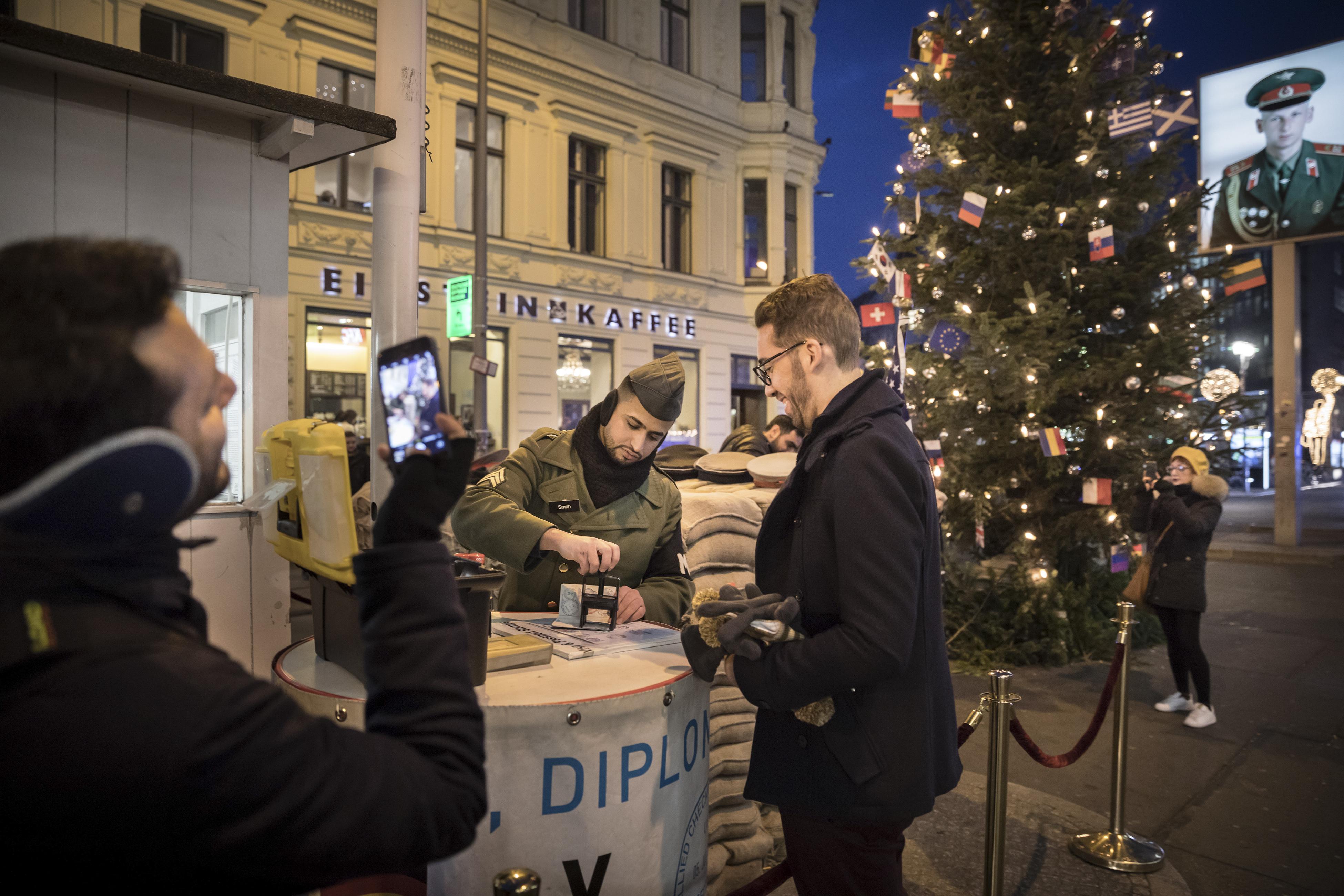Personas disfrazadas de soldados posan para fotografías con los turistas por una cuota en el puesto de control, el cual ahora es administrado por el Museum Haus am Checkpoint Charlie. (Gordon Welters/The New York Times)