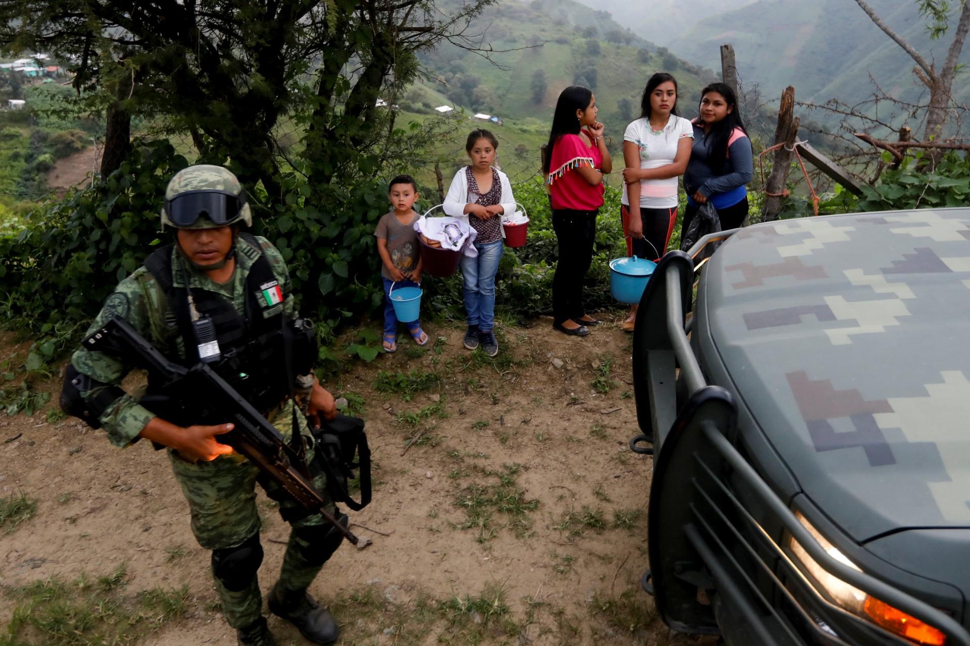 Un soldado se para cerca de los residentes cuando llega al área donde encontraron una plantación ilegal de opio en la Sierra Madre del Sur, en el estado sureño de Guerrero, México, el 24 de agosto de 2018.