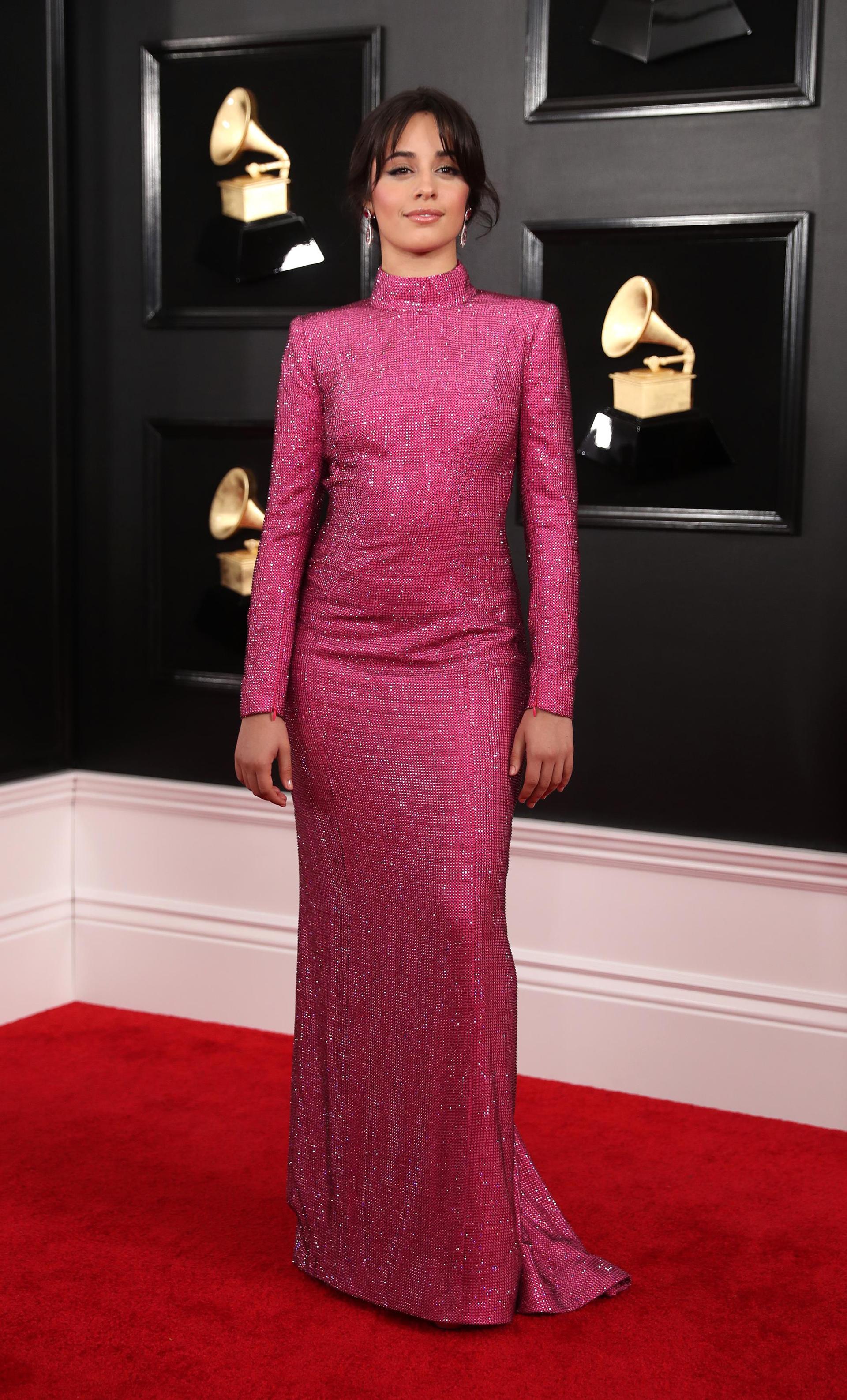 Camila Cabello inauguró la red carpet de los Grammy con un vestido sirena en color fucsia de mangas largas y cuello polera. Lo completó con aros joya en forma de hoja con piedras preciosas