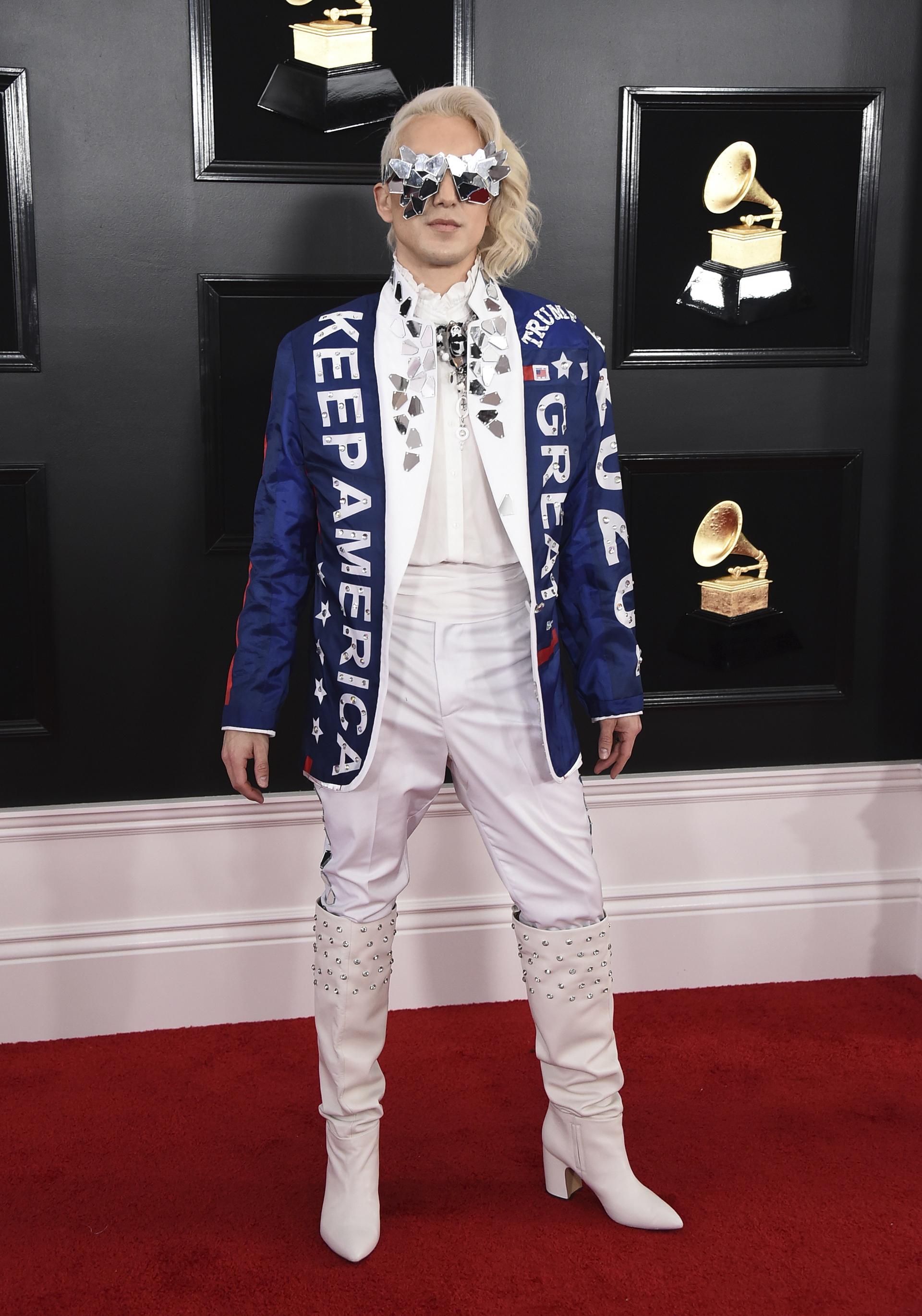 Ricky Rebel en total white, con pantalón, camisa y botas con tachas, el cantante llevó la política nuevamente a la alfombra roja de los Grammy con un mensaje para Trump