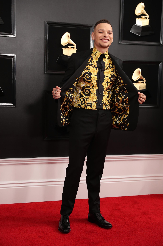 Kanye Brown, apostó al tradicional esmoquin negro pero su camisa y el interior de su saco llamó la atención. Búlgaros y flores en dorado