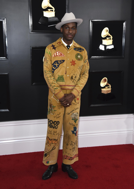 Leon Bridges lució en la red carpet un traje de corderoy en color mostaza con apliques, pintado y bordado con frases y dibujos. Lo completó con botas de cuero negra y un sombrero de baby alpaca en gris