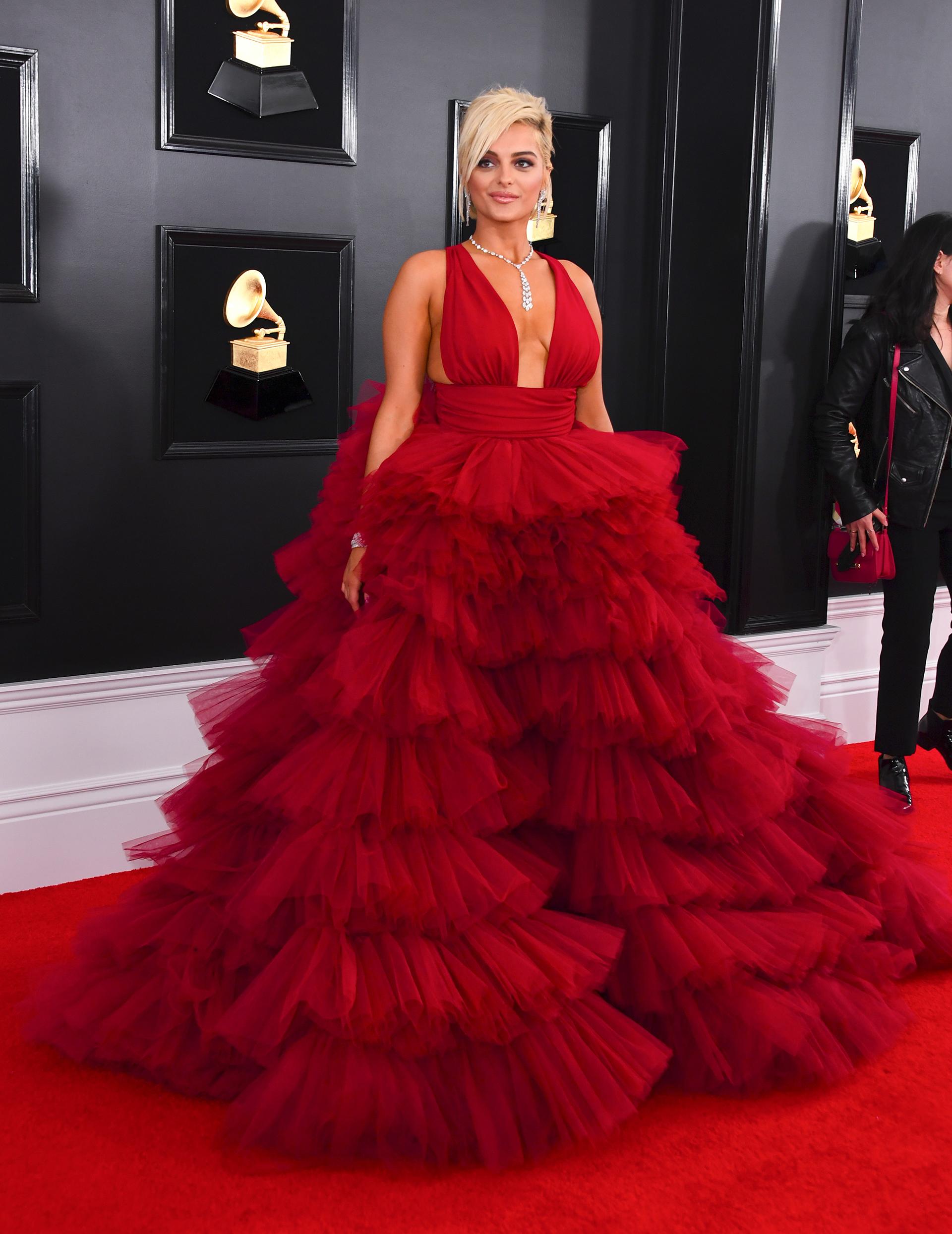 Bebe Rexha apostó a un vestido en rojo pasión vaporoso de tul en cascada. Completó el look con joyas plateadas, un brazalete, un collar y aros colgantes